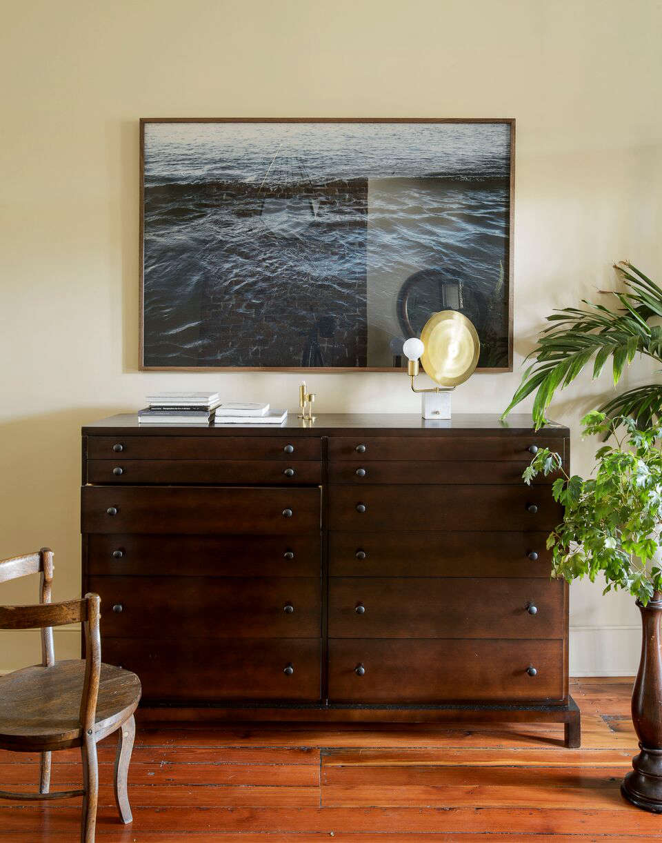 In the master bedroom, a Helios Table Lamp by Workstead sits atop a vintage Robsjohn-Gibbings dresser. The seascape photo is by Charleston-based photographer Jeff Holt.