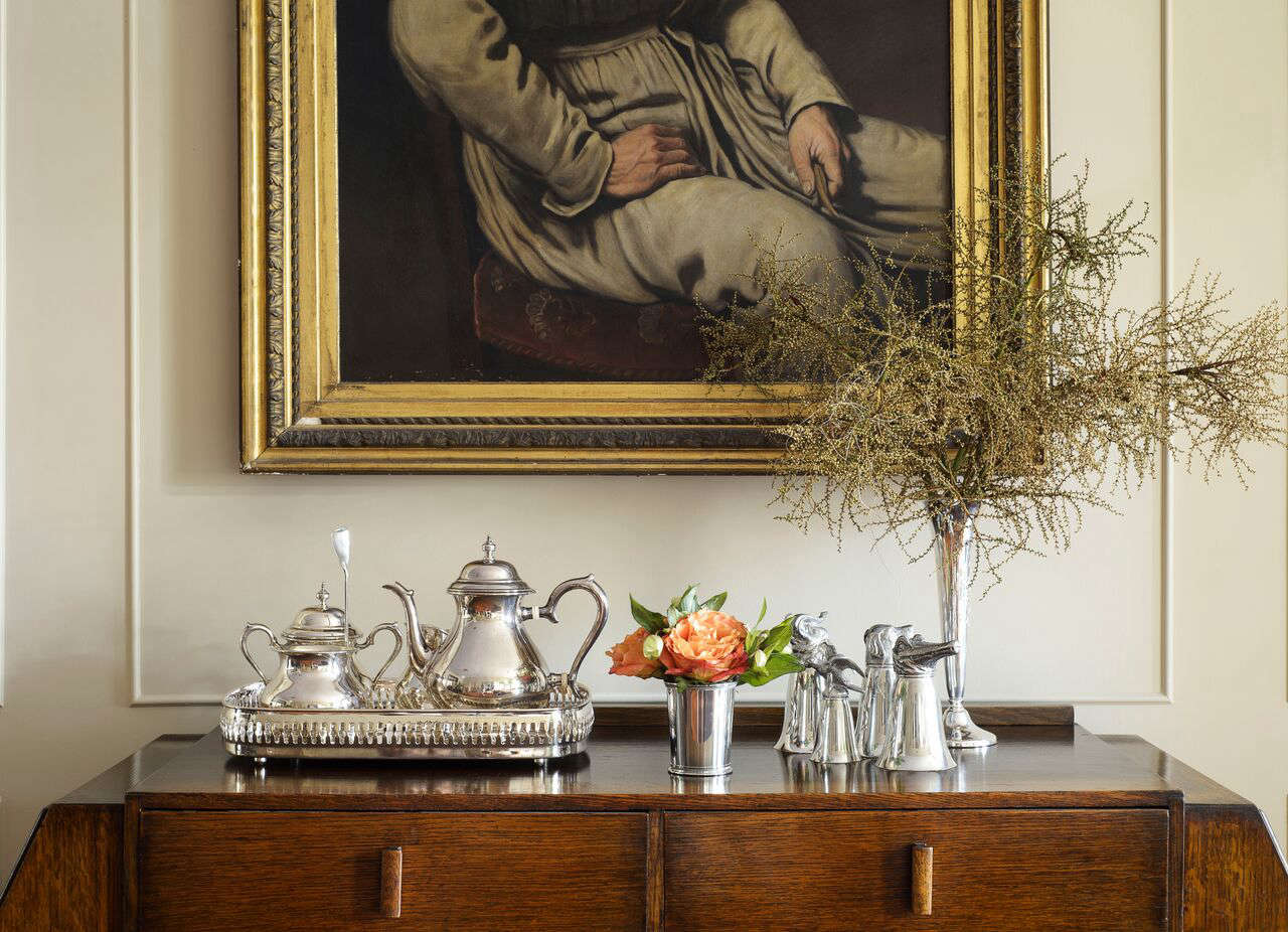 """The sideboard, which we found at a local Charleston antiques store, is a weird Art Deco/Mission mashup; it doesn't know what it wants to be, which is why we love it,"" Robert says. ""The oil painting, by Franklin Tuttle, is from Alex Raskin Antiques in Savannah, Georgia. We think it's a self-portrait because he's wearing a smock and holding a brush. The silver tea set and other pieces are from Croghan's Jewel Box in Charleston; this kind of silver is a very Southern thing. We were inspired by local designer Amelia Handegan, who uses it in her interiors."""
