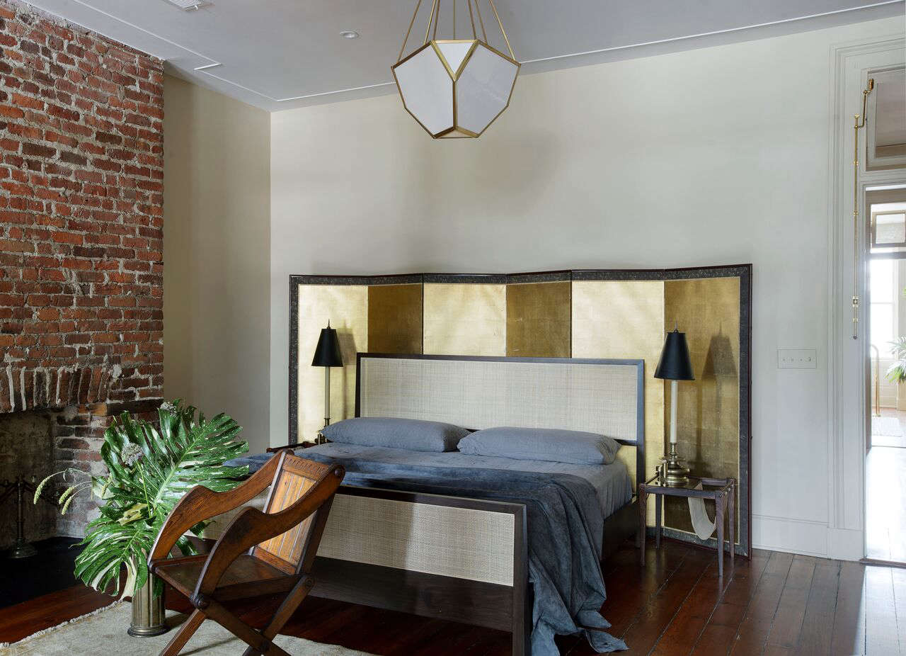 "In the master bedroom, the bed is sited in front of a gilded folding screen found in a Savannah antiques shop; ""It reflects light in an otherwise dark space,"" Robert says. ""The Glastonbury chair is from a church in England; we found it years ago in an antiques shop in the Hudson, and the bedside lighting is vintage."" The Yves Hang fixture in hewn brass with polished brass accents and white pot glass was designed by Michael Amato for Urban Electric."