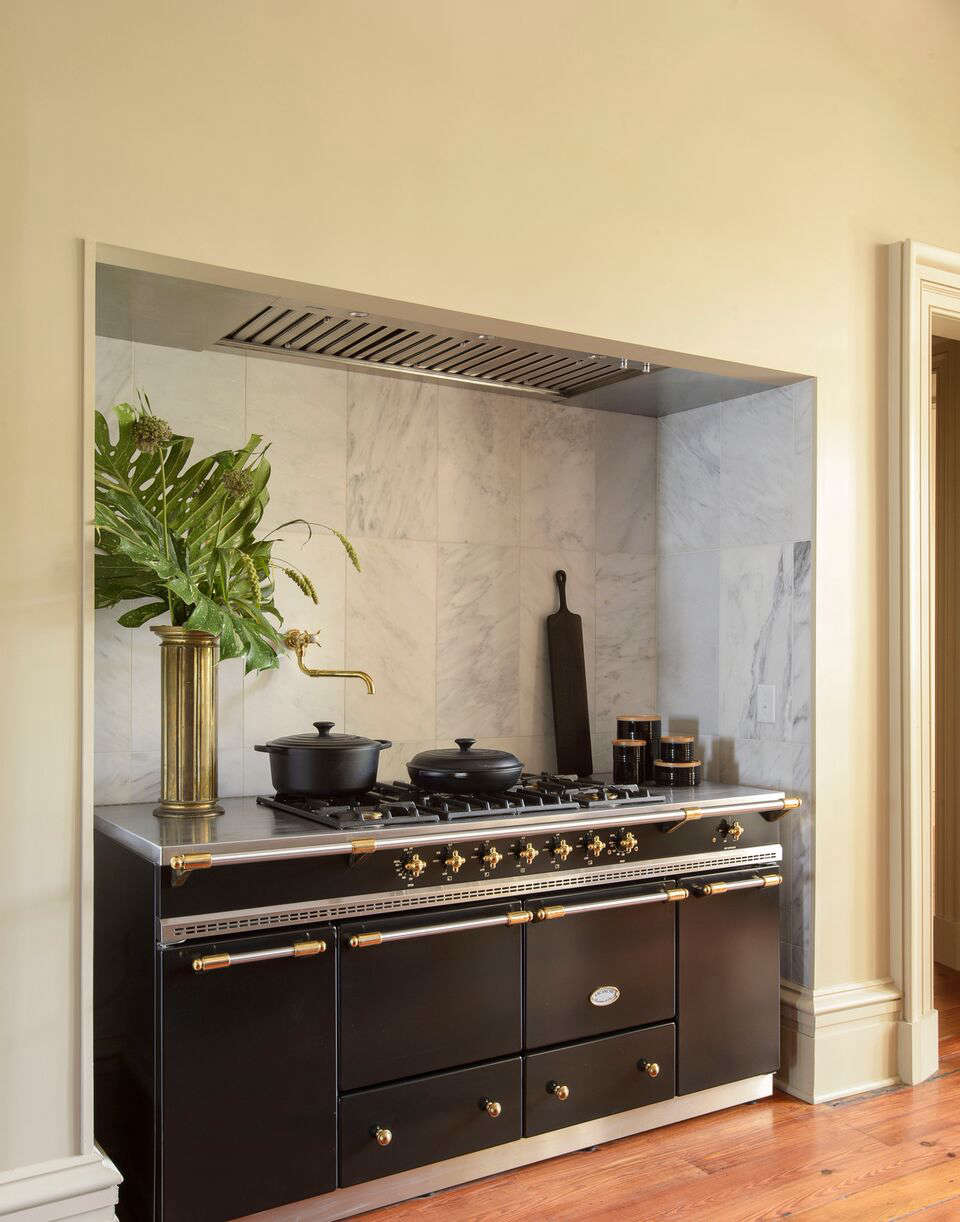 A Lacanche range is tucked into a marble-tiled niche. A Blackline cutting boardfrom Josh Vogel is propped in the corner.