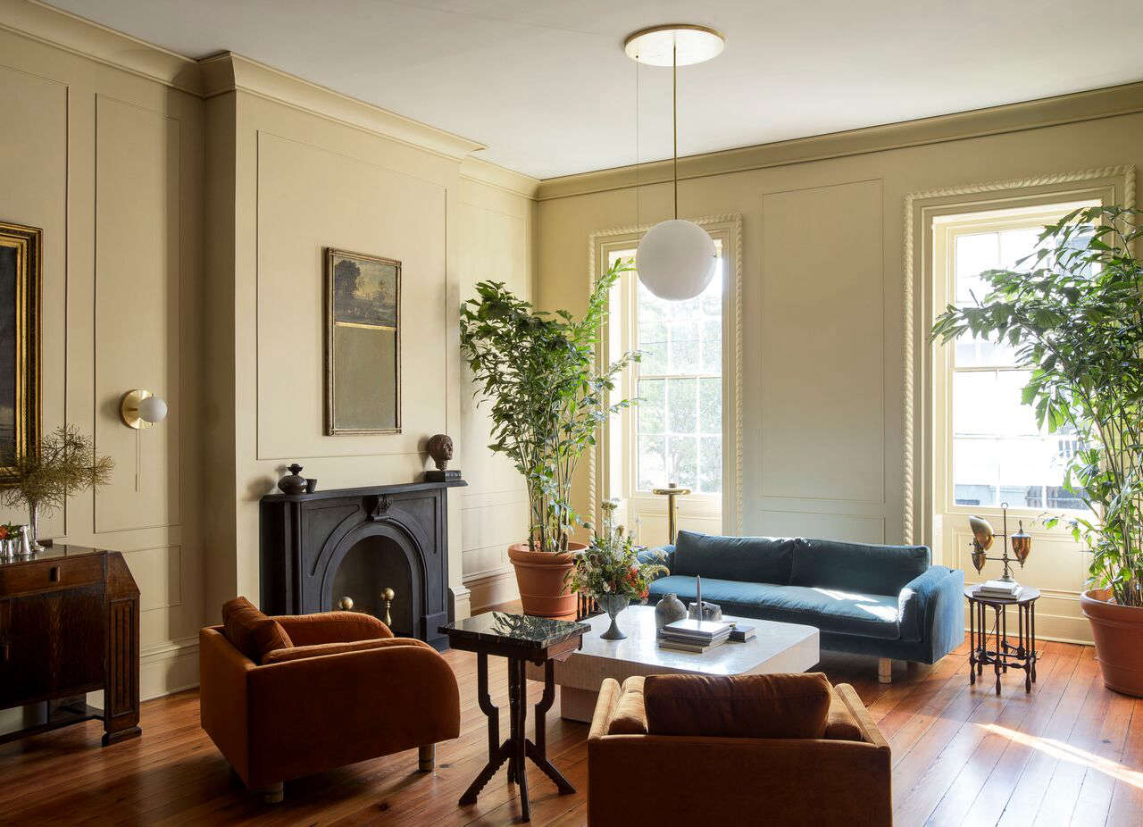 "In the living room, lighting by Workstead includes a Signal Wall Sconce and a Signal Globe pendant. Many of the pieces throughout the project are vintage, including the marble-topped side table positioned between the Lawson-Fenning chairs. ""We wanted that tension between old/new and high/low,"" Robert says. ""We have an appreciation for the sculptural qualities of vintage furniture."""