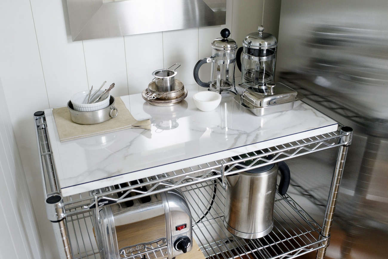 Architect Barbara Chambers topped a metal slatted shelf in her kitchen with a small piece of marble to create a functional surface, which she uses as a coffee and tea station. See the rest of her house at An Exercise in Order with Architect Barbara Chambers.