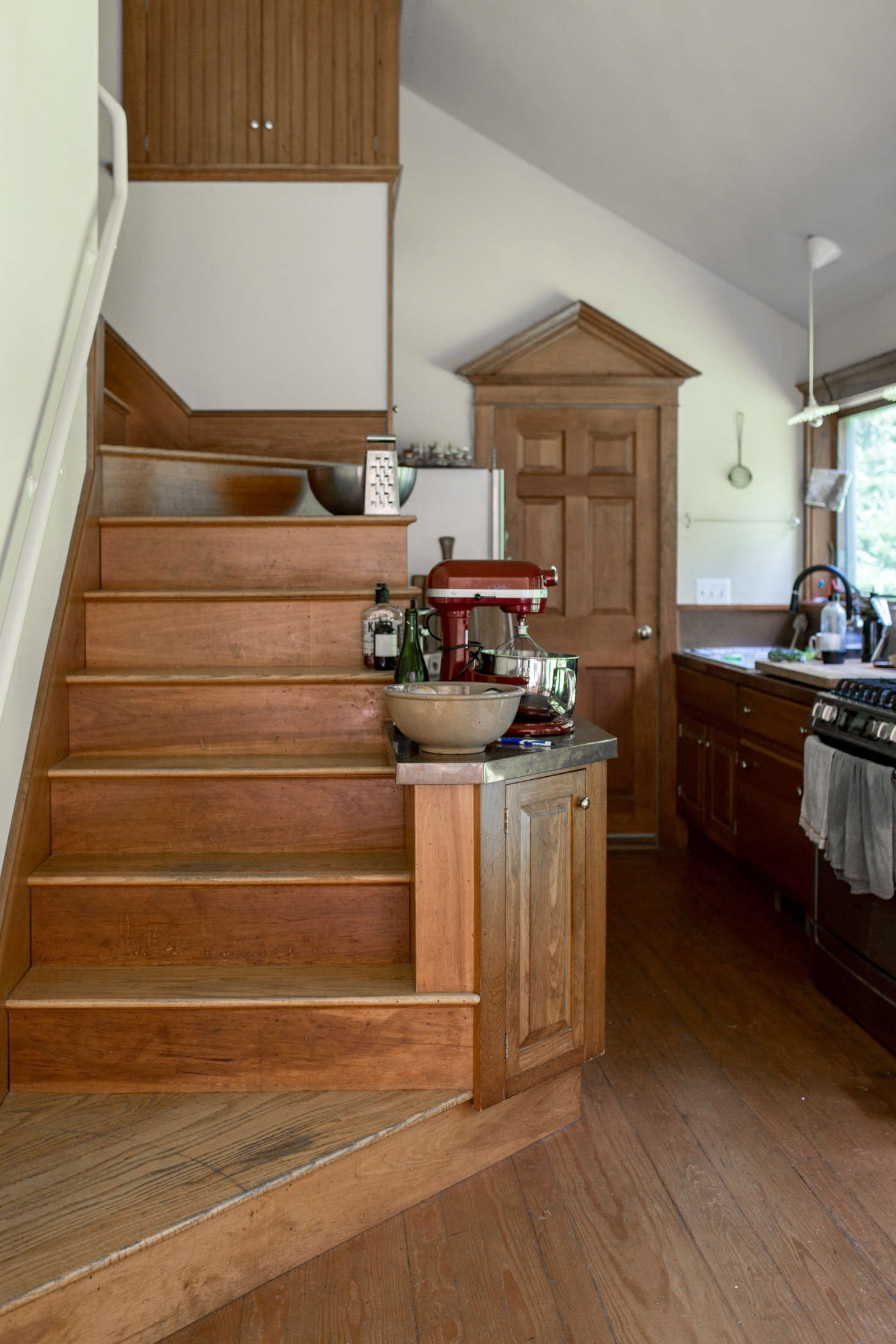 The kitchen is tucked beside the staircase; the couple made only a few small tweaks, including installing copper countertops.