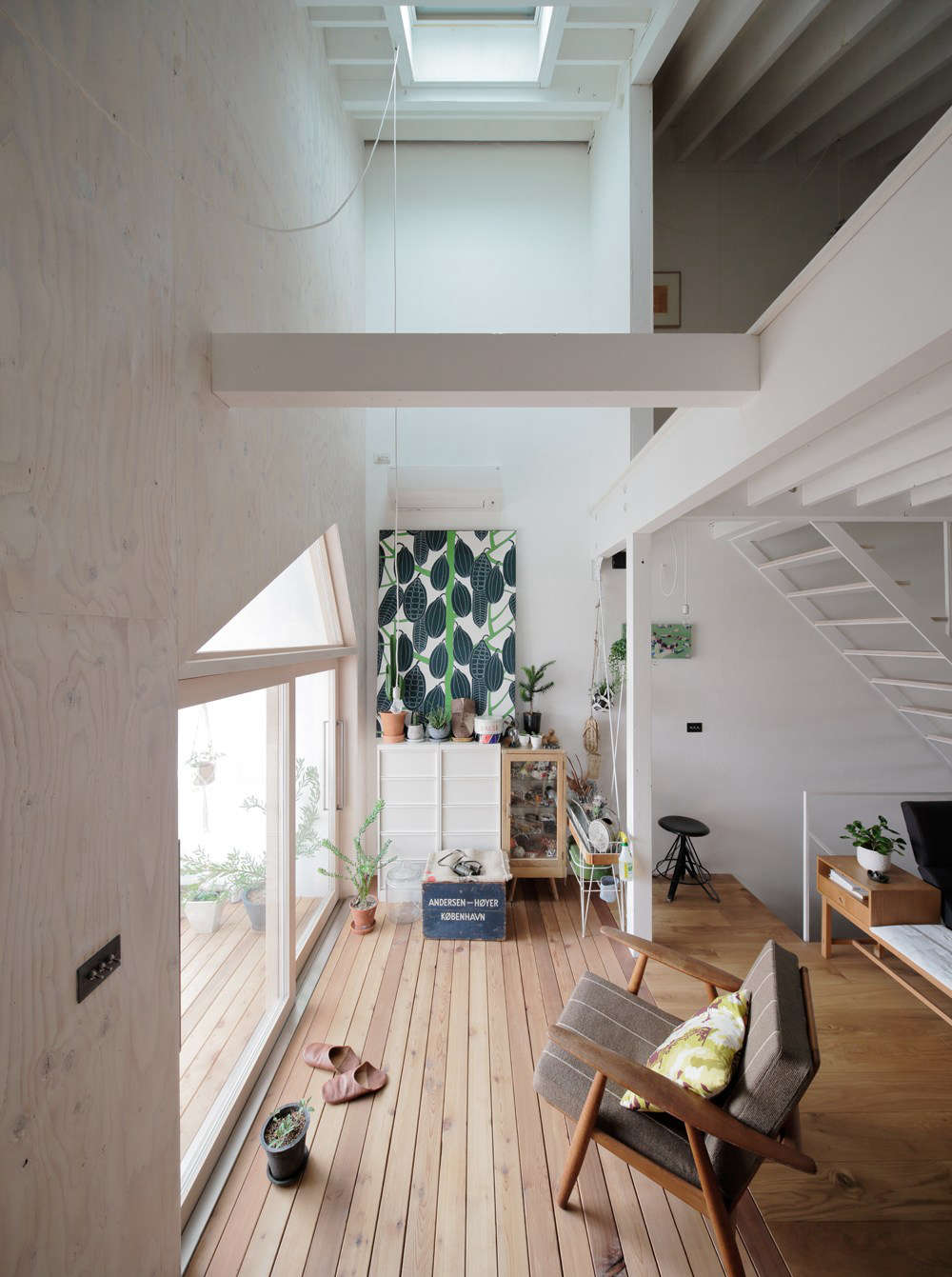 The living area is oriented to the front, south-facing balcony and brightened by a skylight. That's the bedroom overhead.