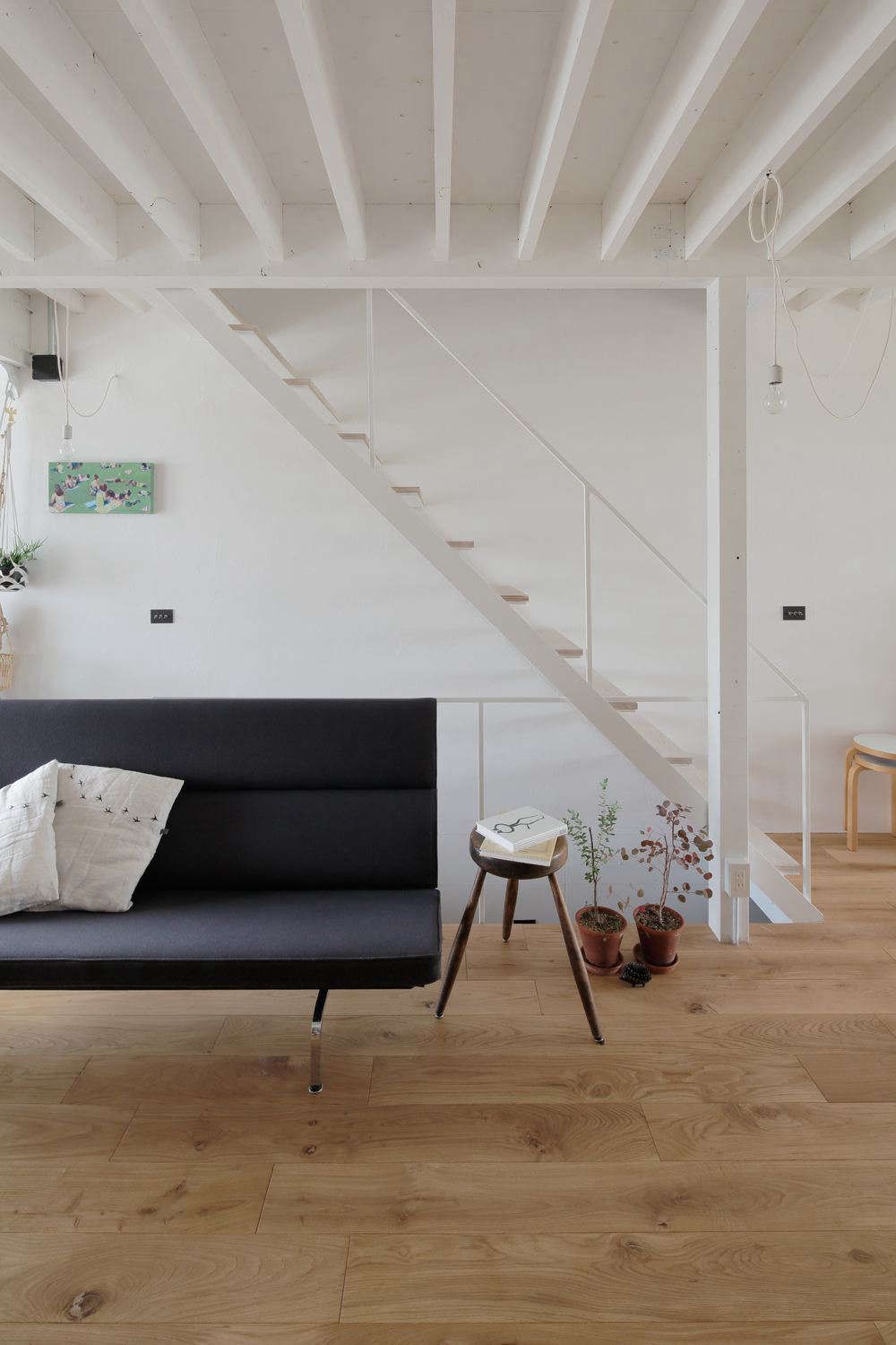 "The ceiling beams and wooden stair treads play off each other in a rhythmic pattern. ""The owners can see the underlying structure and can customize the house easily,"" Hirano says."