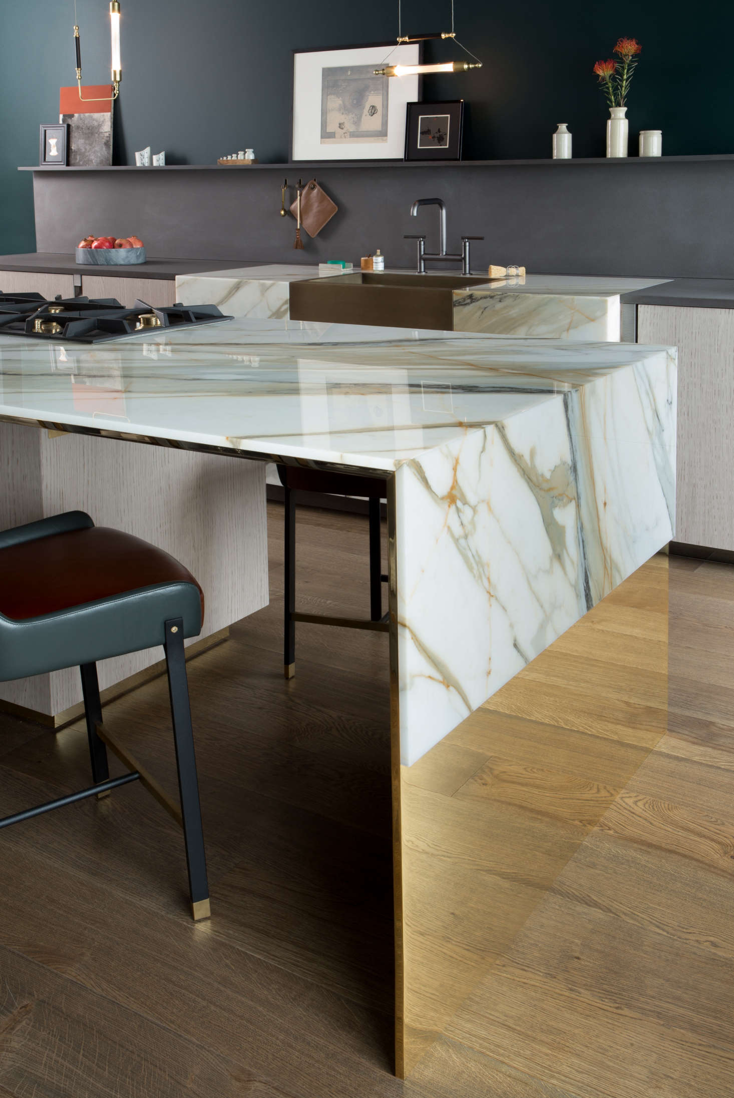 "Calacatta Borghini marble is ""draped"" atop the polished brass island, so that the richly veined stone looks like a luxe version of humble oilcloth."