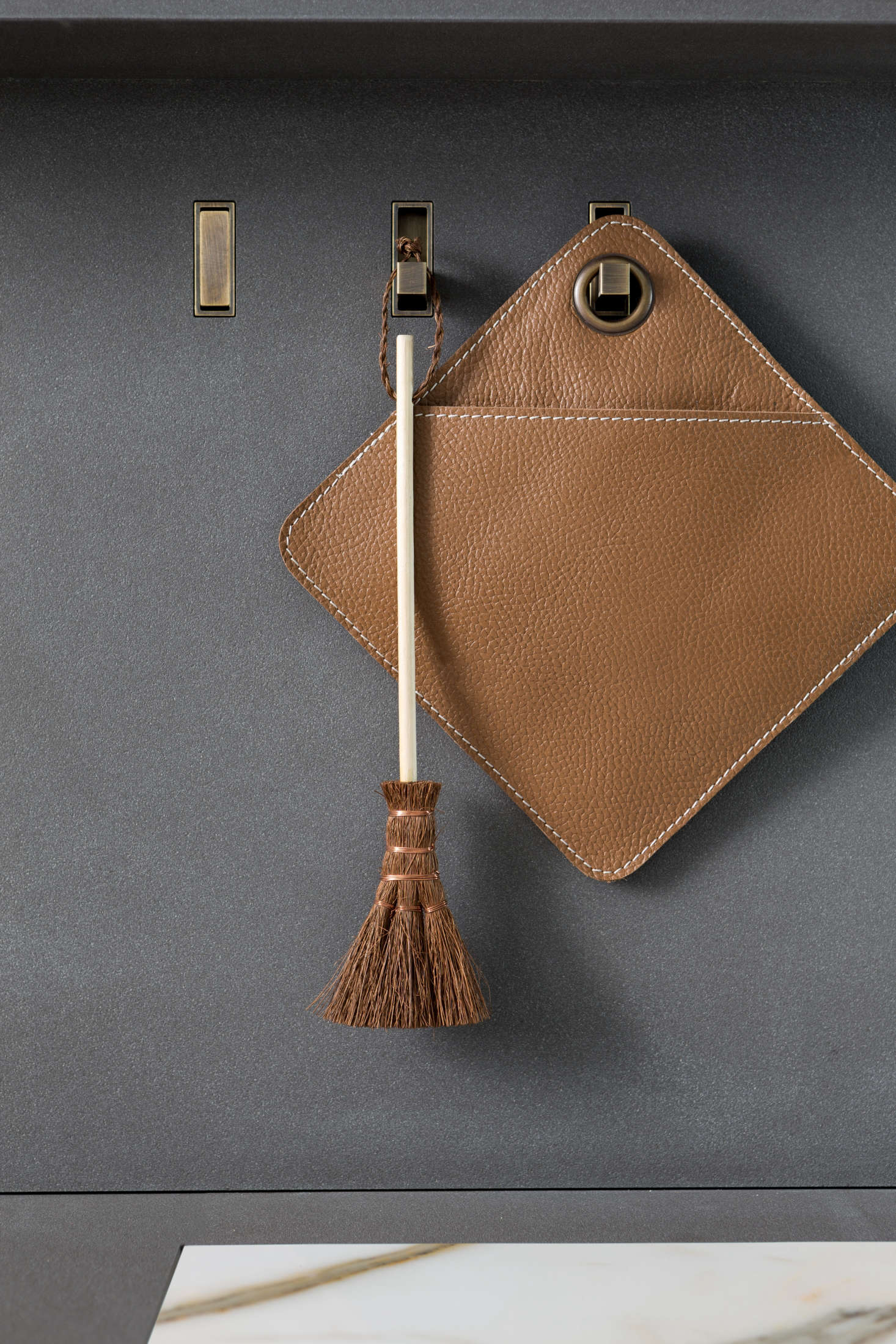 "Retractable brass ""secret hooks"" hold elevated versions of the kitchen essentials. Admiring the potholder? See 5 Favorites: Rugged Leather Potholders."
