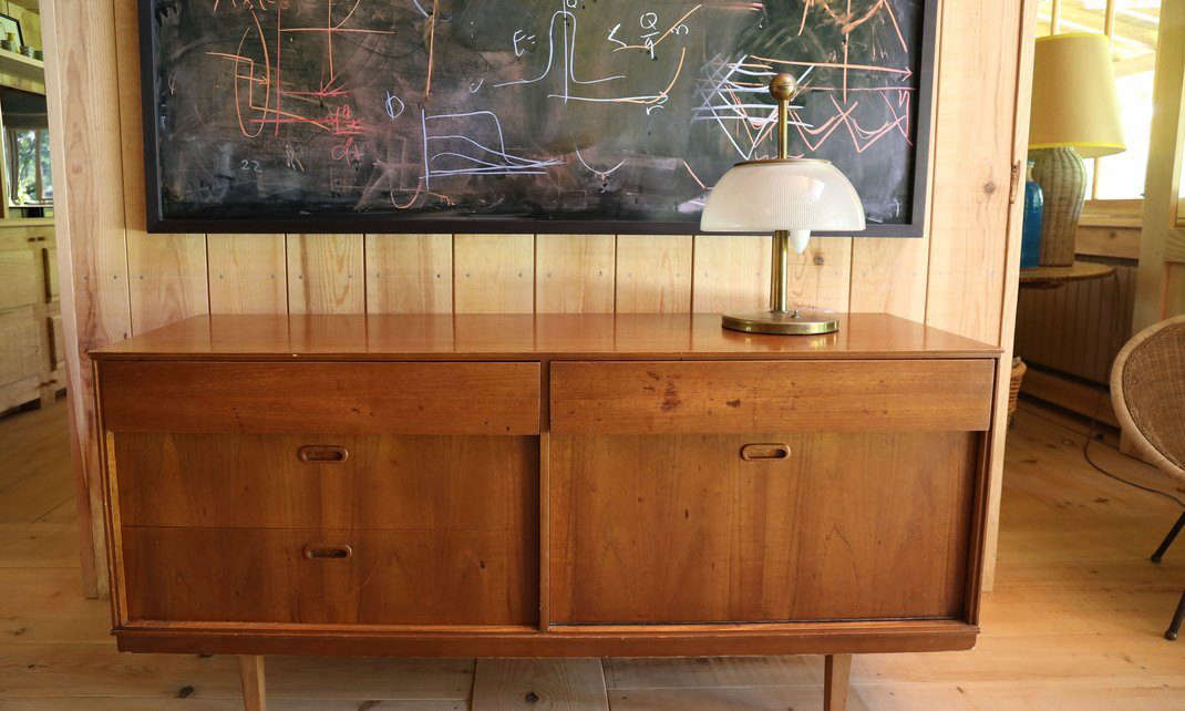 A midcentury credenza is topped by a vintage lamp.