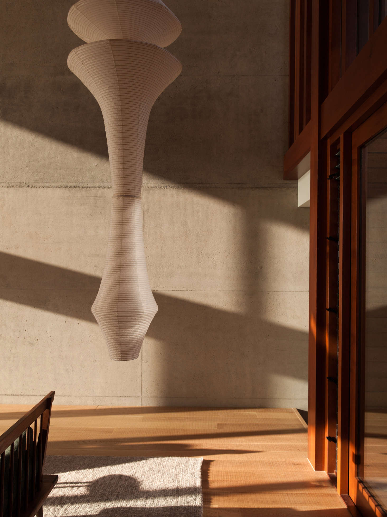 A Noguchi Akari Light Sculpture Model E hangs above a New Zealand wool rug.