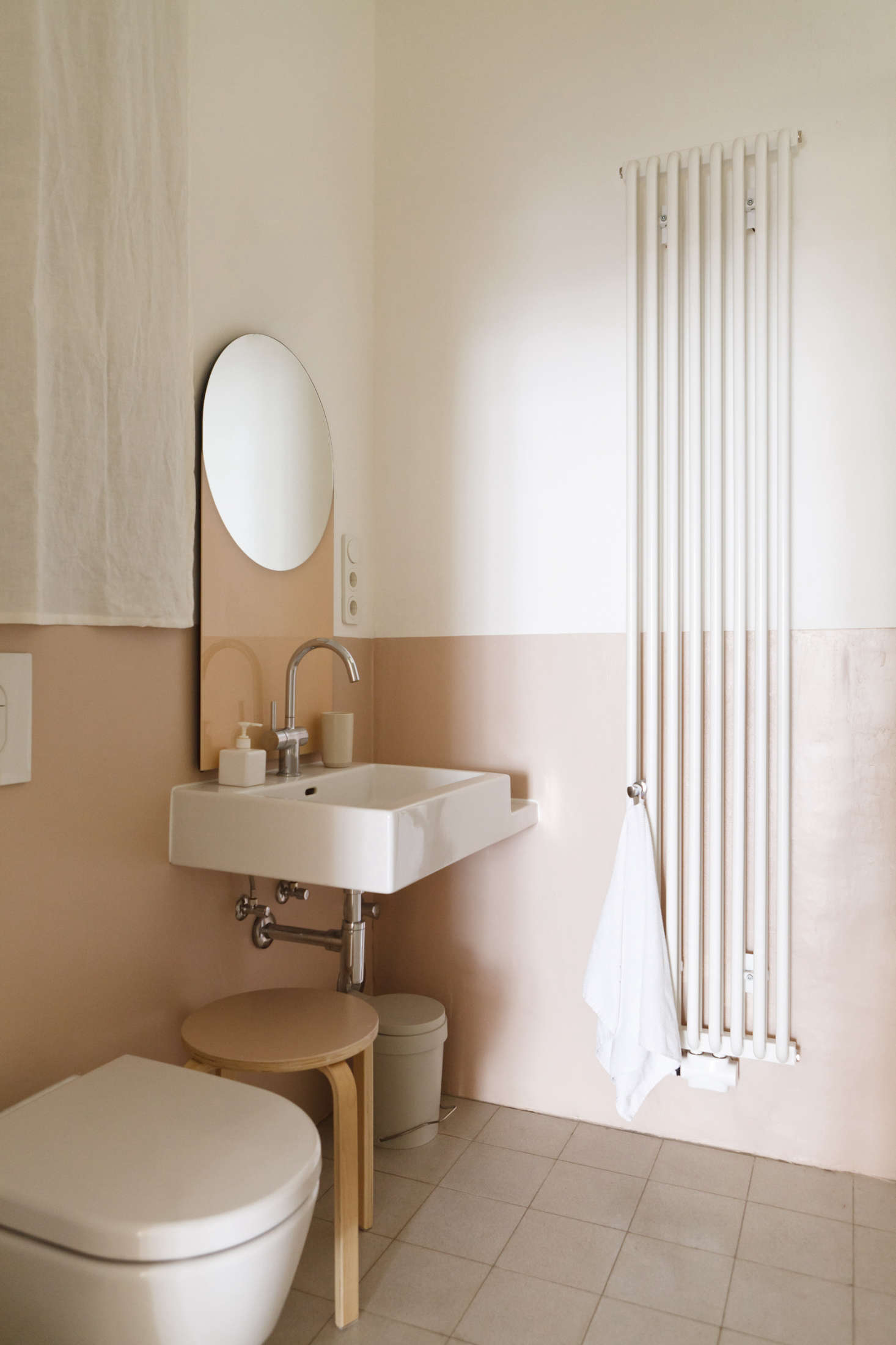 In a Berlin apartment, designers Studio Oink painted the lower half of the bathroom wall in rose.