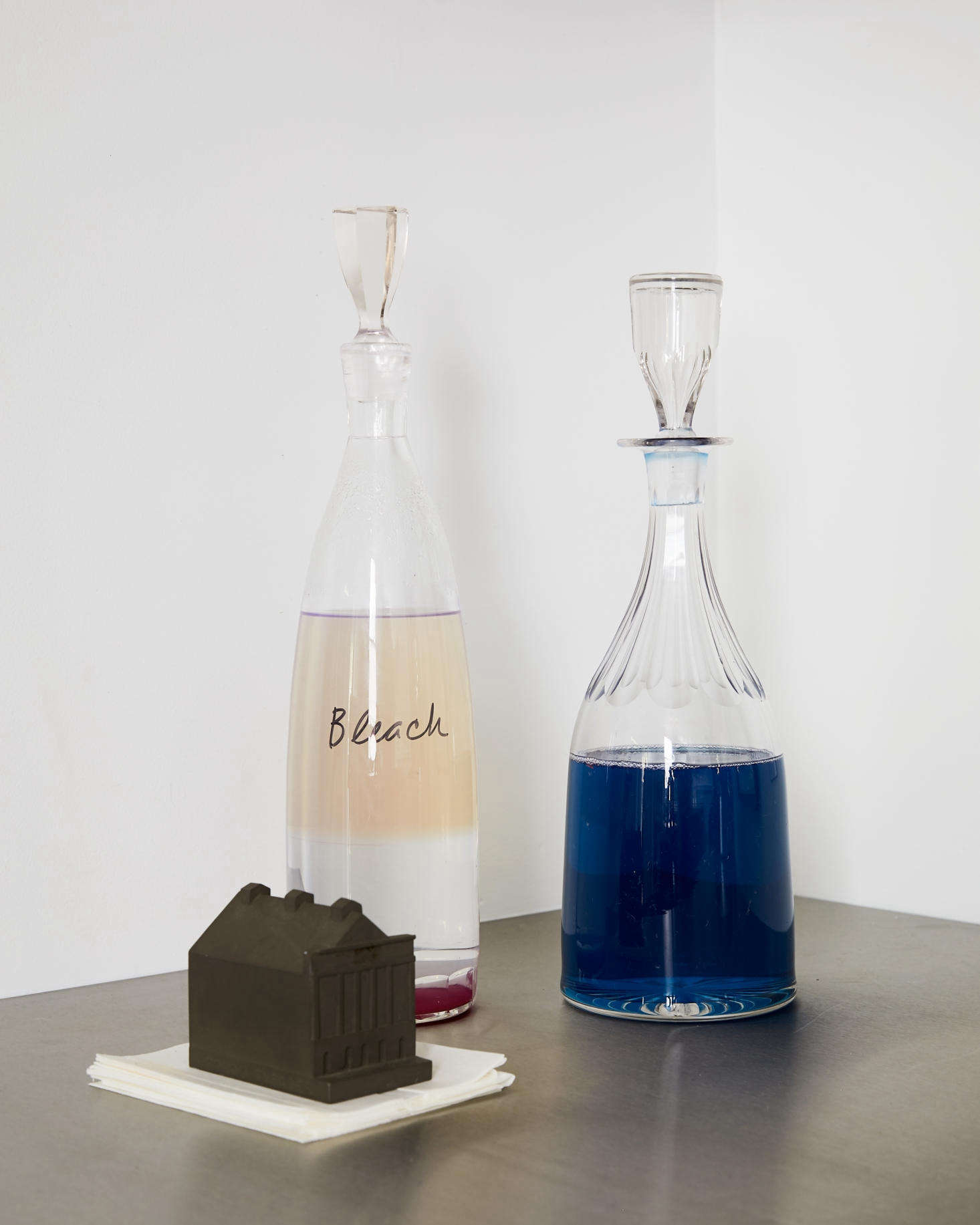 Amy keeps her laundry detergent and bleach in vintage crystal bottles. A stack ofColor catchers is anchored by a mini Ford Theatre inspired by the Buildings of Disaster series by Constantin Boym and Laurene Leon Boym.