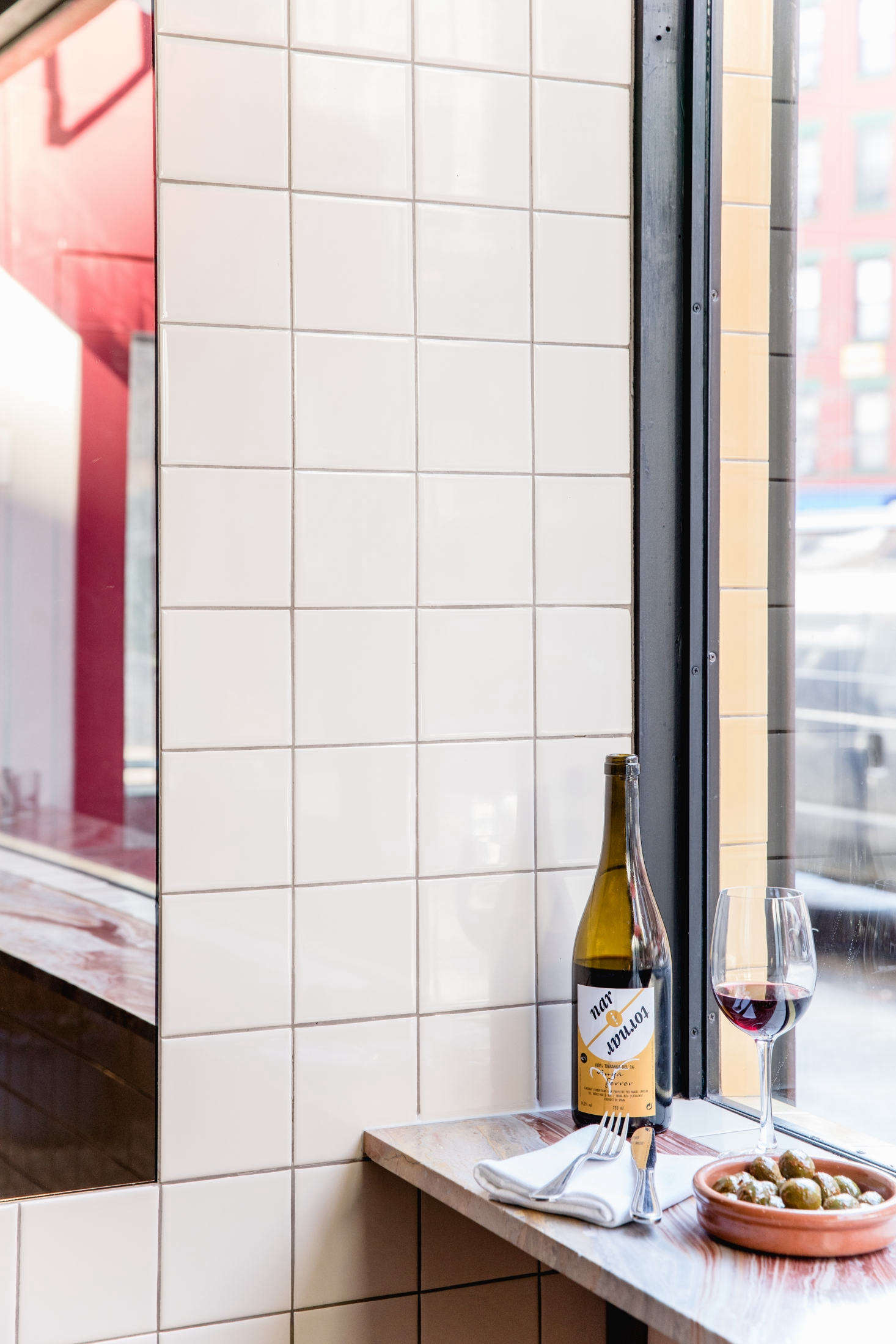 "Another artful shelf/counter: The statement marble ledge in the front window of NYC wine bar Cervo's started as a discarded piece at a marble yard in Greenpoint, Brooklyn. ""They have lots of scrap pieces left over from bigger jobs,"" the owners say. ""We spent a couple days going through all these marble scrap yards looking for one that would work with the rest of the color palette."" For a full tour of the interiors, see Cervo's: 15 Design Ideas to Steal from a Tiny Portuguese Wine Bar in Manhattan."