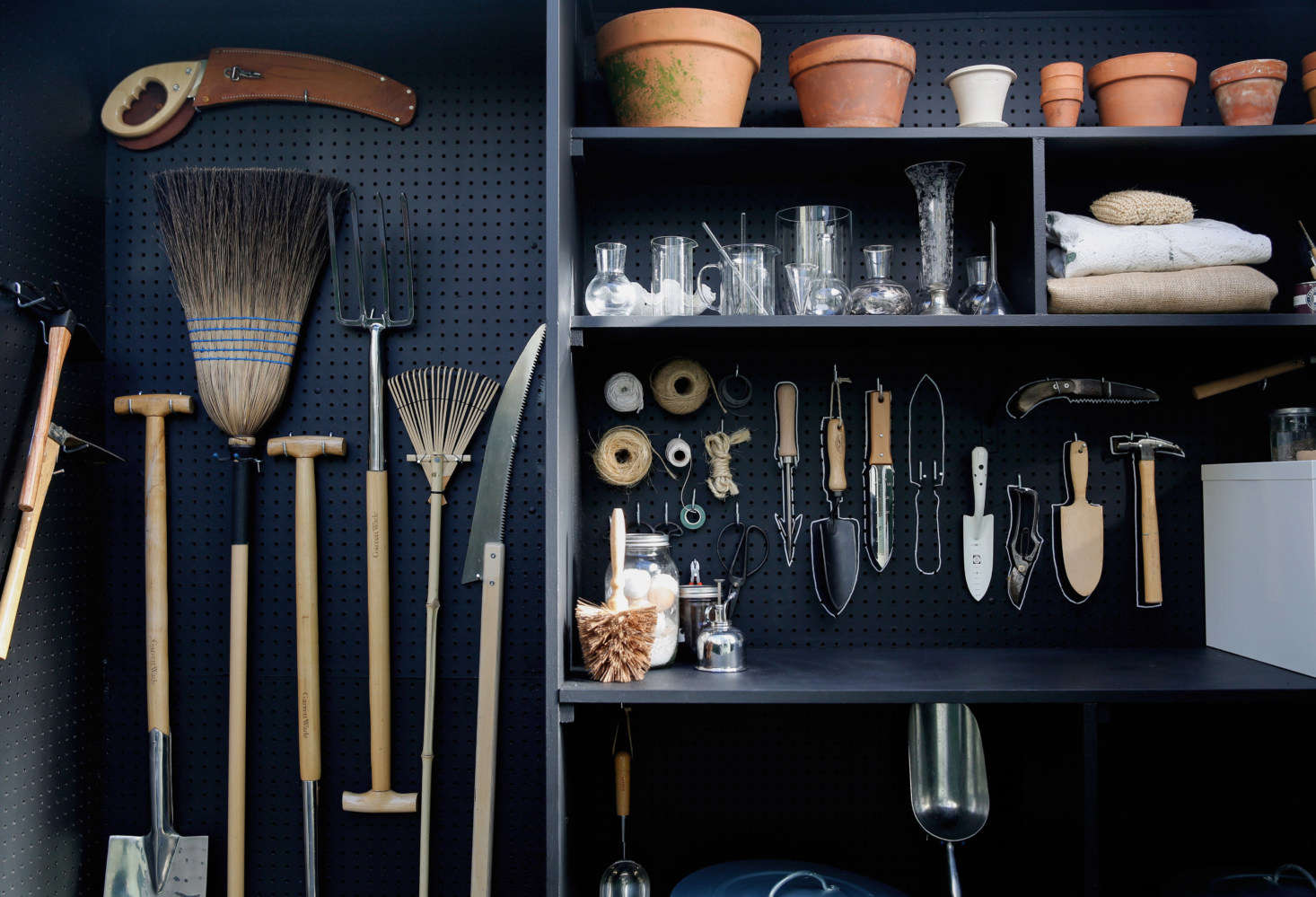 Long-handled tools like rakes and brooms hang on one side of the shed.