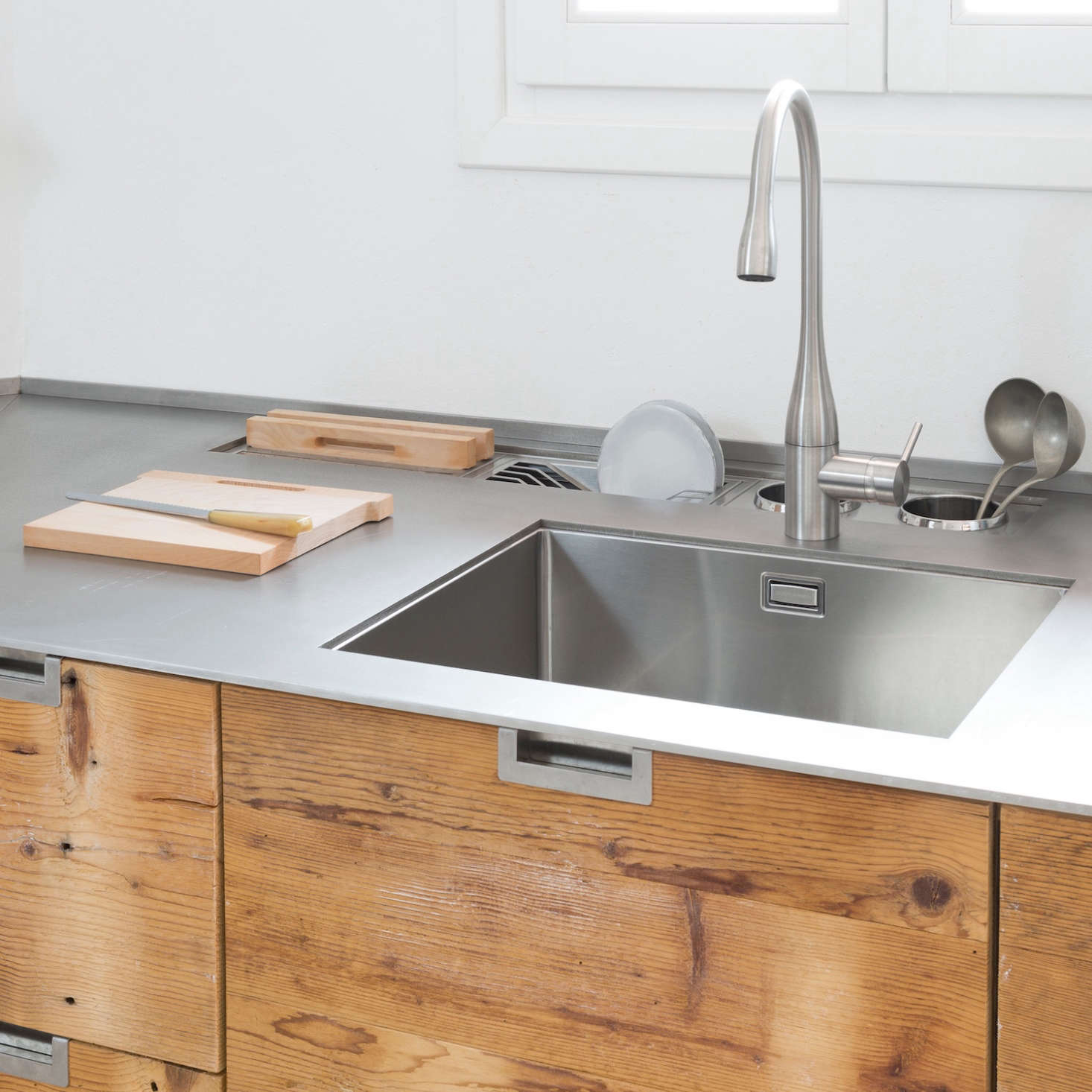 Behind the sink there is a stainless steel clothes horse, a slot for cutting boards and two caddies for kitchen utensils.