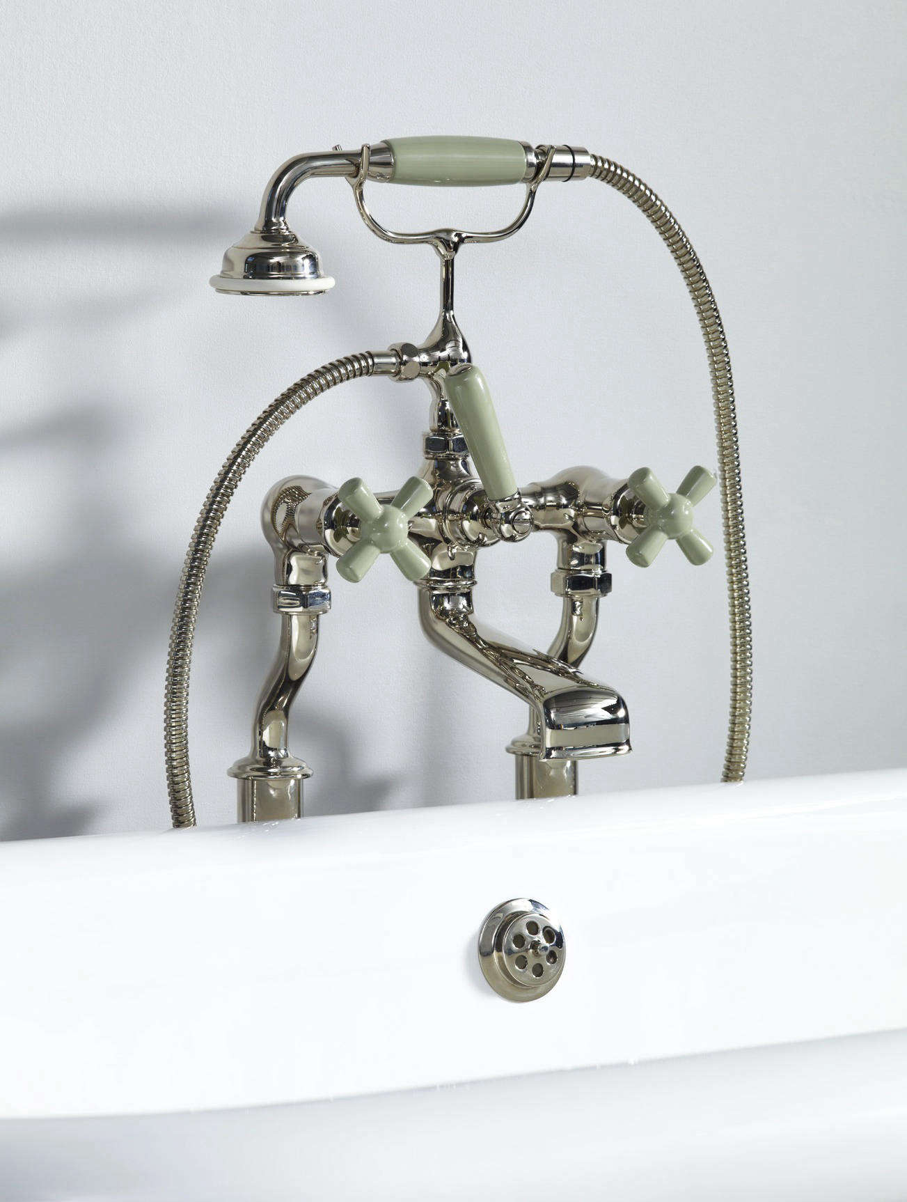 The Rockwell Bath Shower Mixer with Free Standing Legs, shown in Willow Green, pairs with freestanding bathtubs and can be ordered with colorful crossheads and handgrip; £1,282.