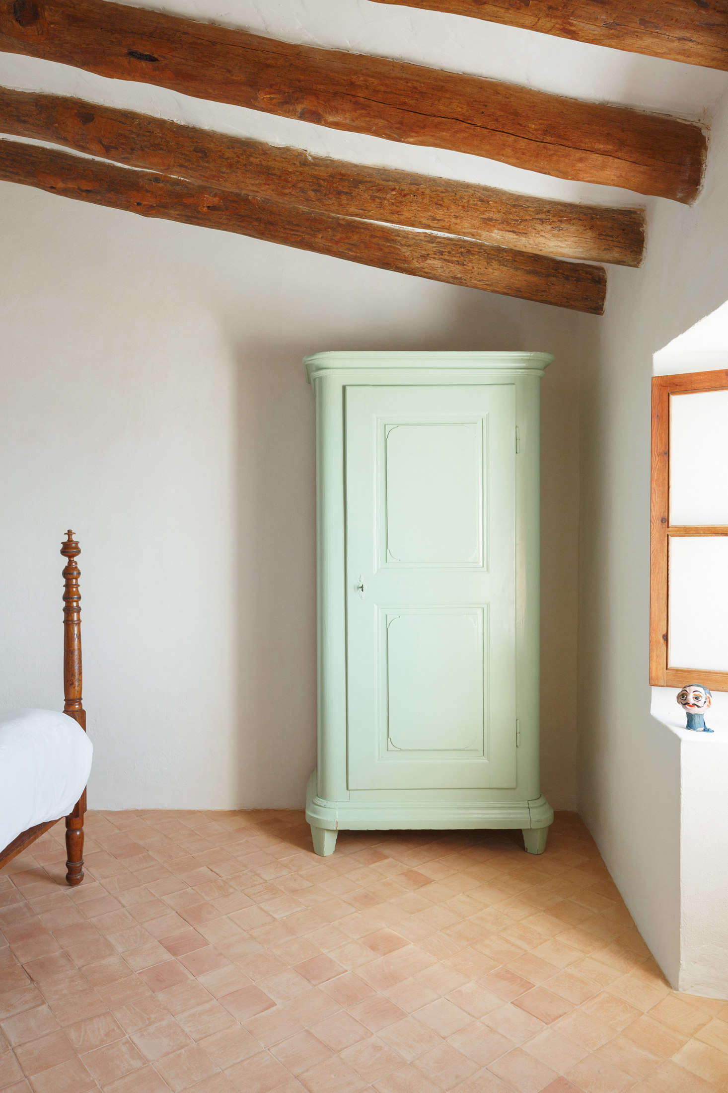 """At the foot of another bed: """"a green armoire, bought as-is in a brocki in Basel."""""""