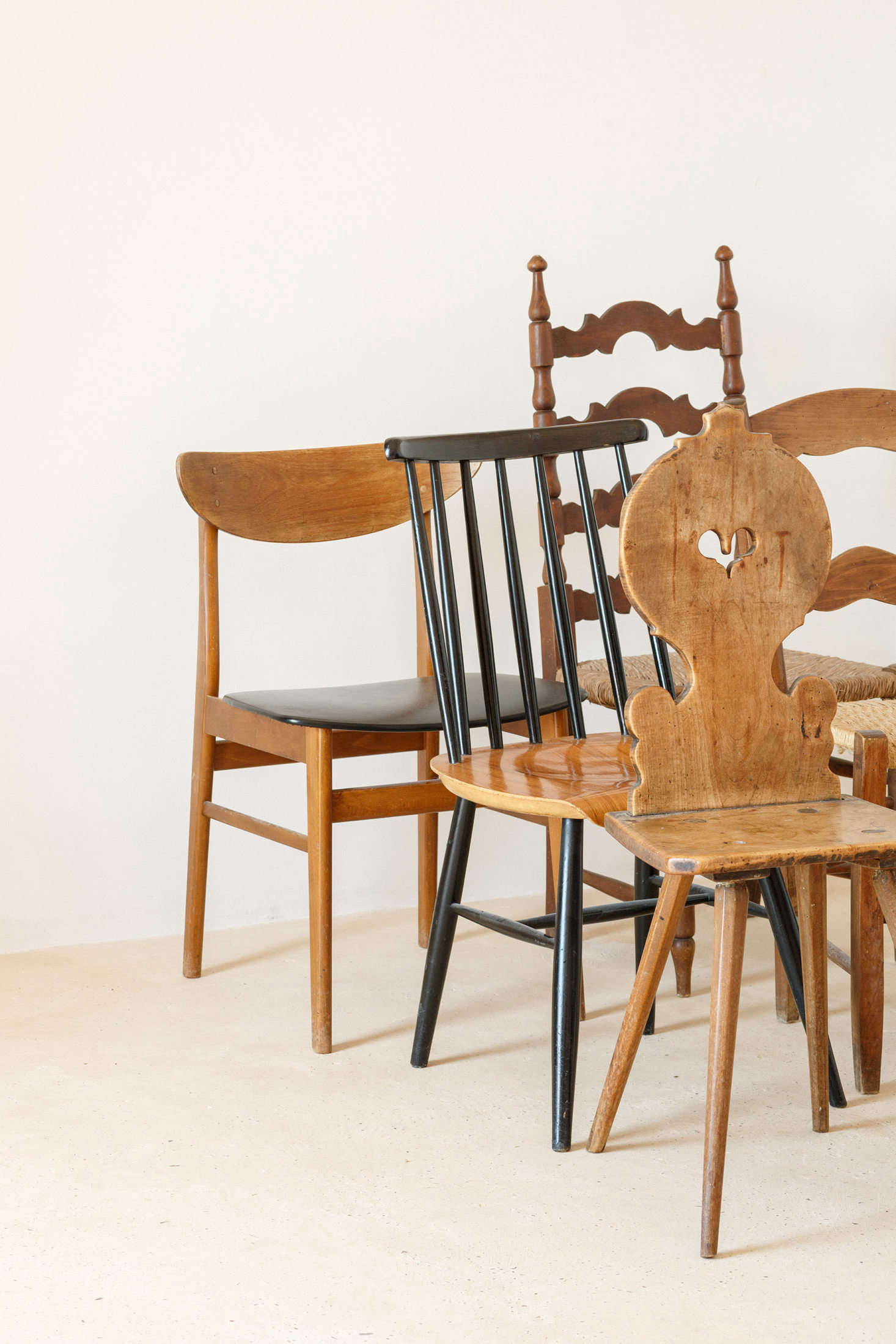 """The chairs throughout the house are a mix of styles: """"some existing Mallorcan-style chairs that were in the house (luckily the previous owners kept all existing furniture), some Scandinavian chairs bought in Basel and in flea markets in Paris and Belfort, an Eames Vitra Wire Chair from Basel, and a traditional Swiss wooden chair, bought in a brocki (a secondhand shop, typical in Switzerland),"""" the architects say."""