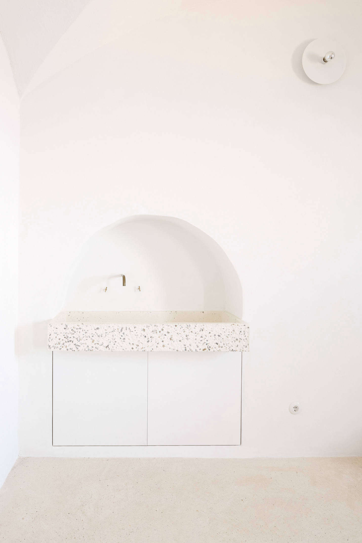 """Palencia and Colón preserved a small archway in the kitchen and installed a custom tinted-concrete sink by local company Huguet, a reference to Mallorcan stone sinks. Two cabinets underneath store cleaning products and house the waste bin. Of the subtle white light overhead, the architects say: """"It's a lamp designed in 1976 byGeorg Gisel for Lehni, a Swiss furniture company that also produces an aluminum furniture series by Donald Judd, among others. It's a simple round white aluminum plate hosted in a standard ceramic lamp holder."""""""