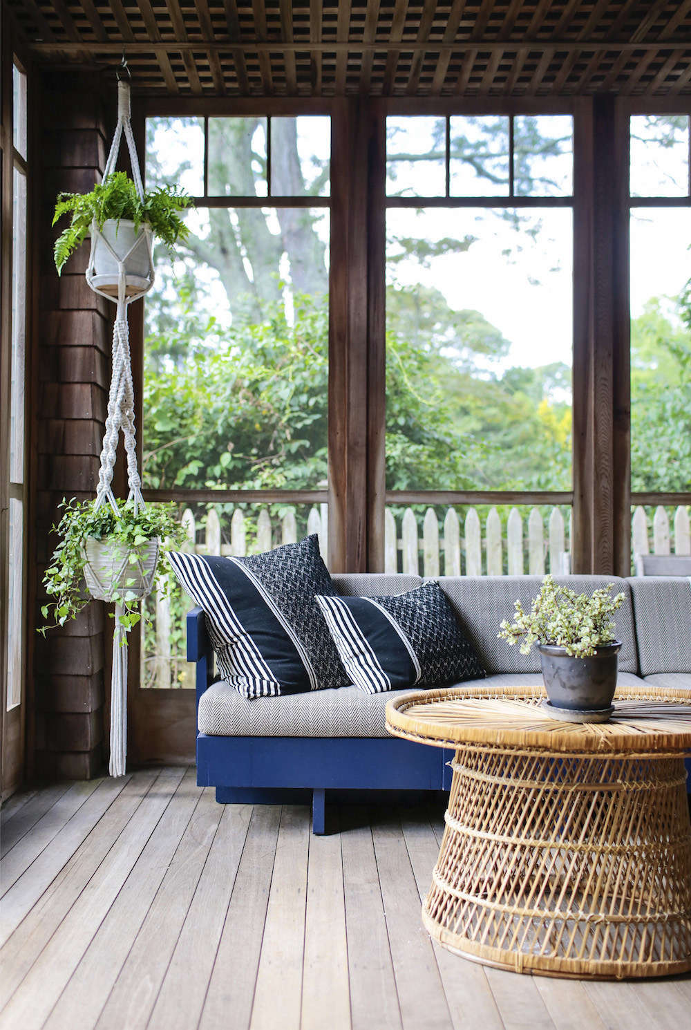 Elizabeth bought the sun porch sofa at auction and had it painted blue and reupholstered. The macramé plant holder is from CB2.