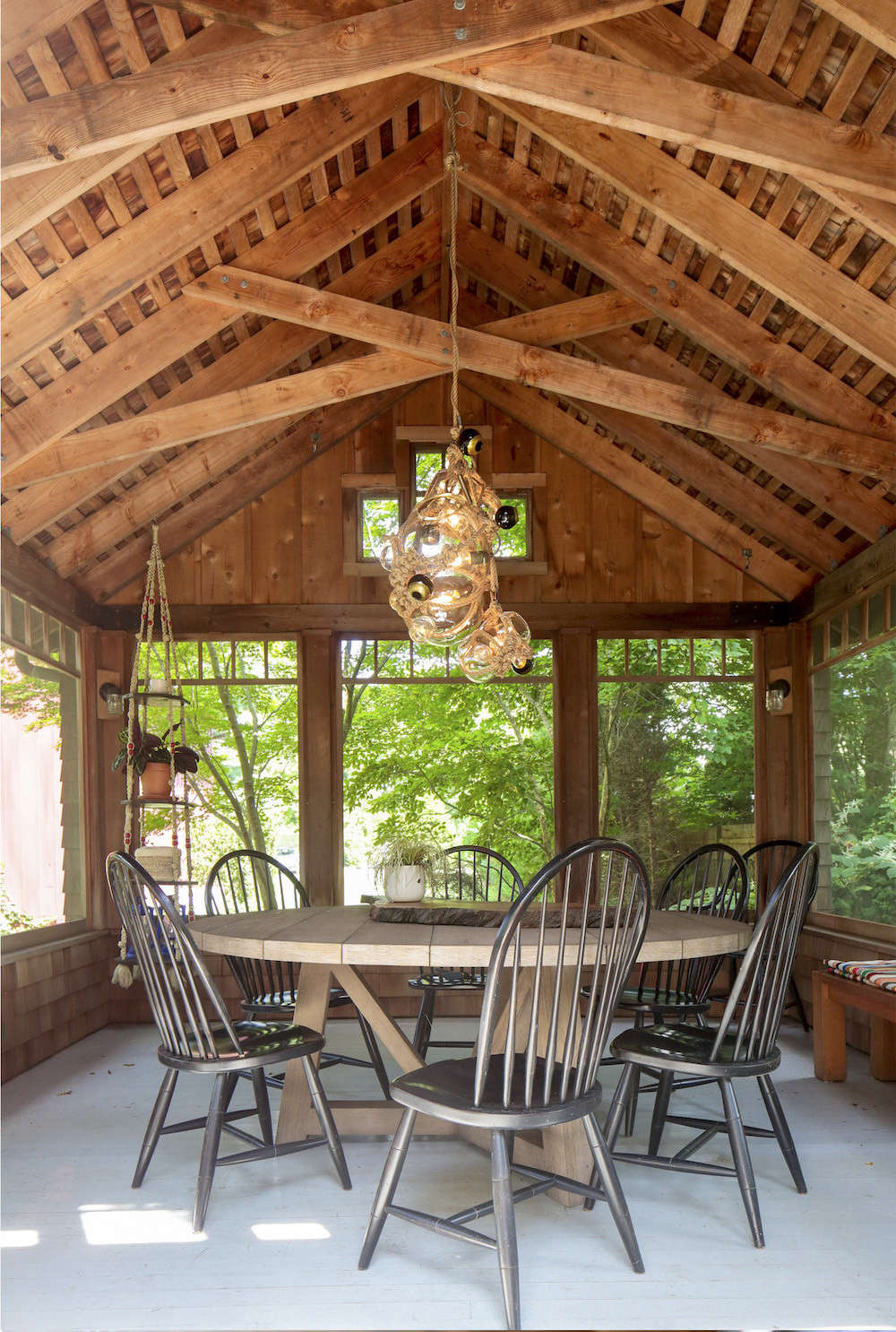 At one end of the porch, Elizabeth has created an outdoor dining area. For a similar shade of gray for the flooring, consider Benjamin Moore's Stormy Monday. The Knotty Bubble chandelier by Lindsey Adelman was inspired by Japanese packaging, buoys, and shibari.