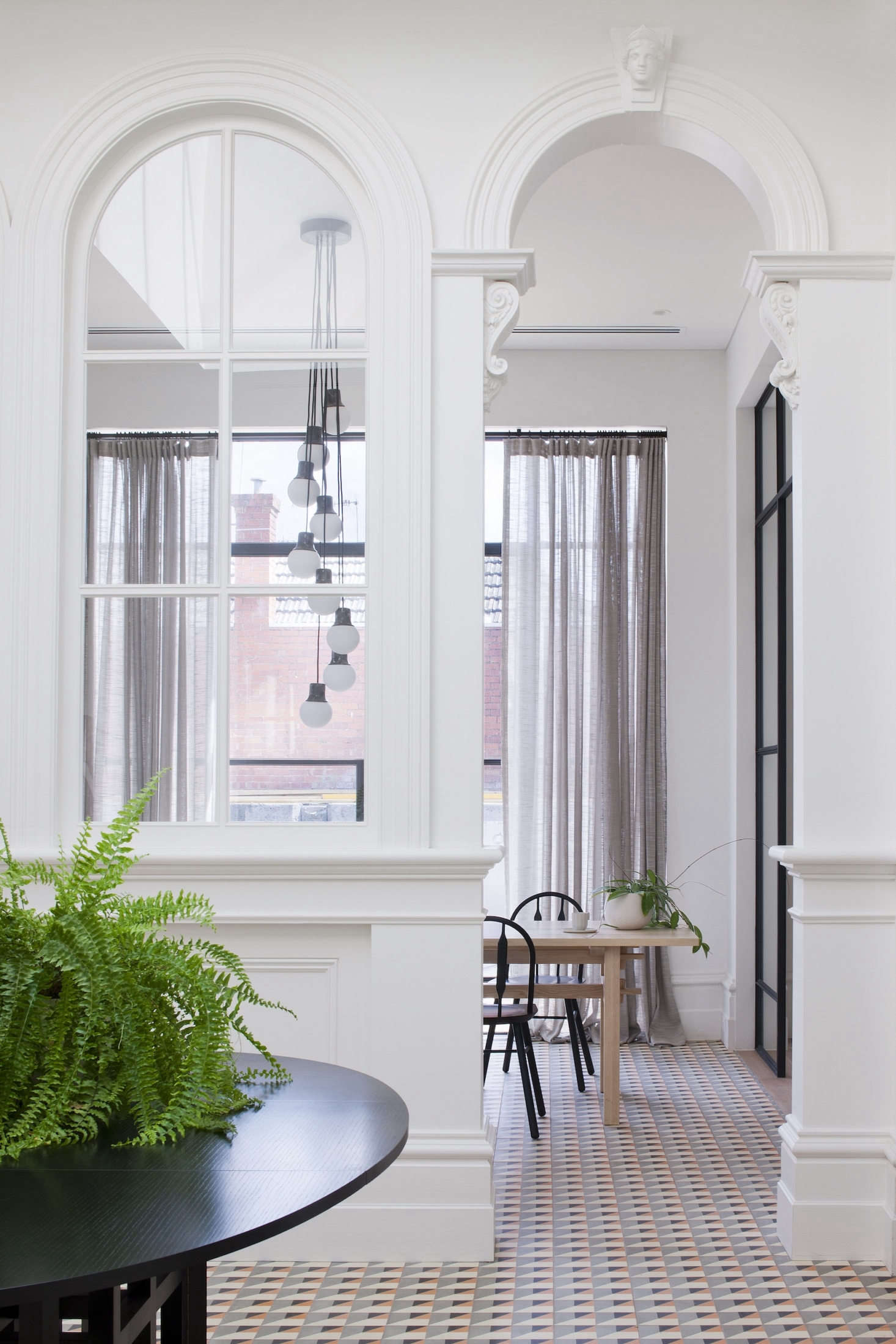 The designers retained the layout of the grand Victorian entryway, adding coral and blue geometric tile throughout the front room, paired with a black Cassina dining table.A new skylight allows natural light to pour in.