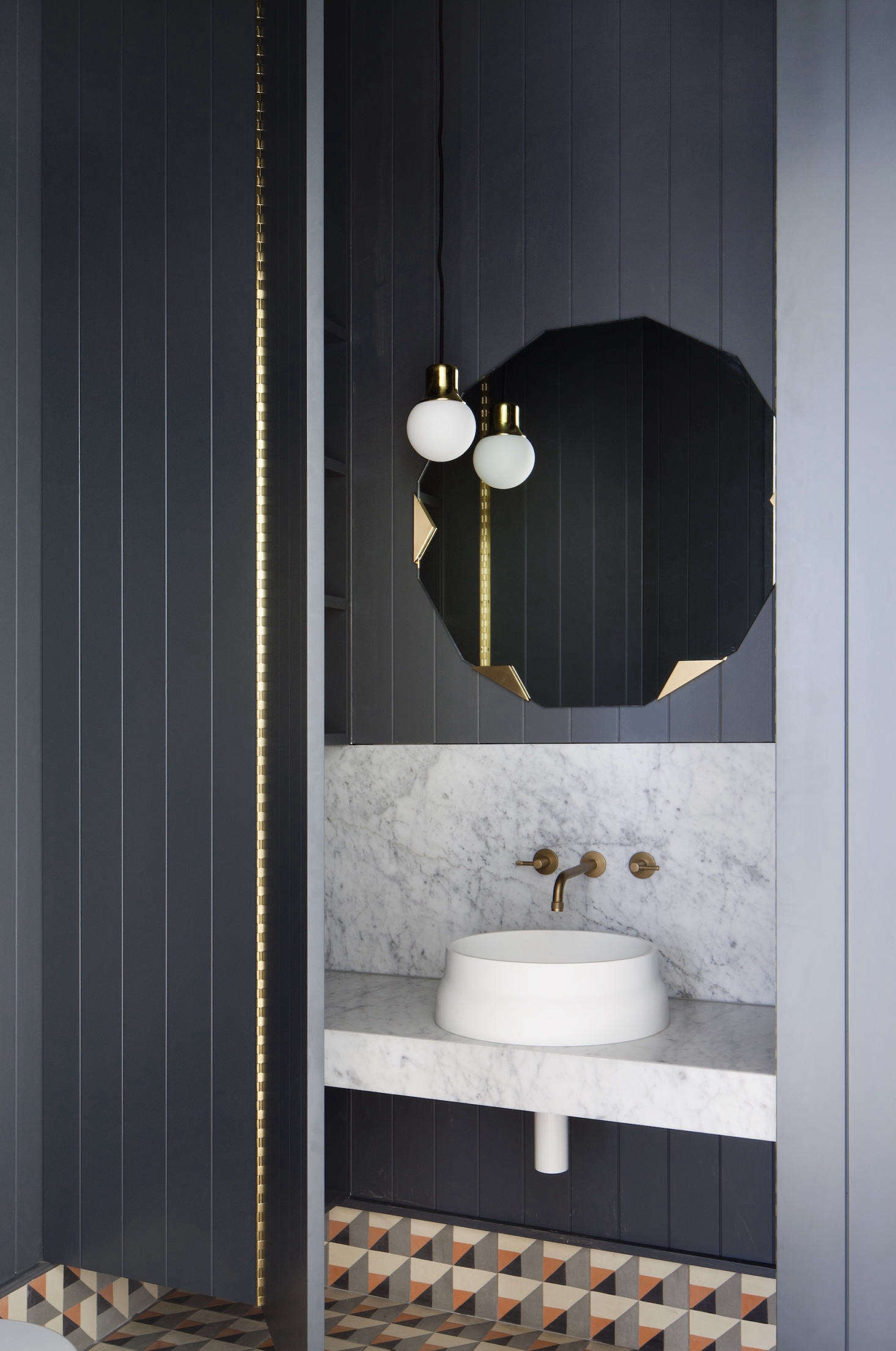 In the powder room, aLatis sink from Omvivo sits on a marble countertop with backsplash.