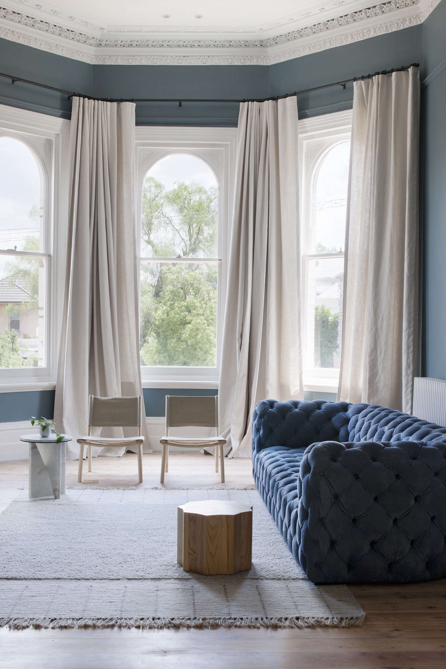 A Paola NavoneChester Moon Sofa in blue anchors the living room. Off-white linen curtains add privacy to the street-facing front room.