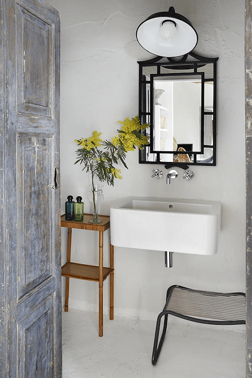 The bathroom is lit by a black wall light, similar to the one over the kitchen.