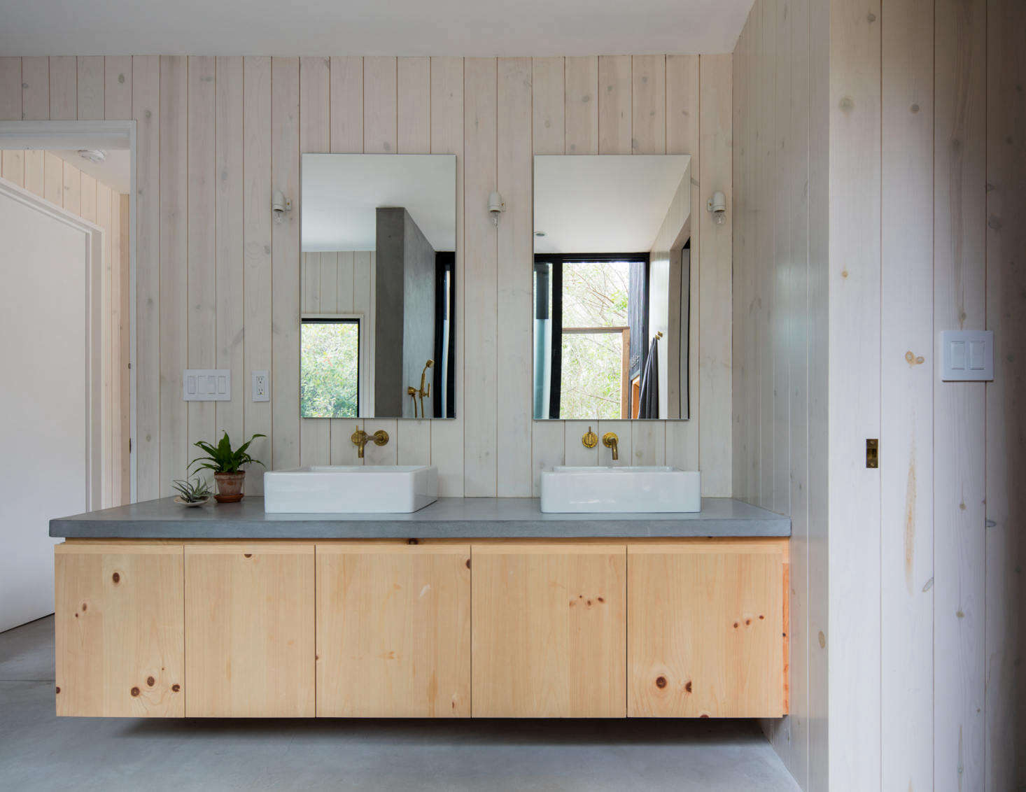 There is one full bath in the house, shared by the family, a decision made early on to maximize living space. The vanity has cabinets of heart pine wood in a clear stain. &#8