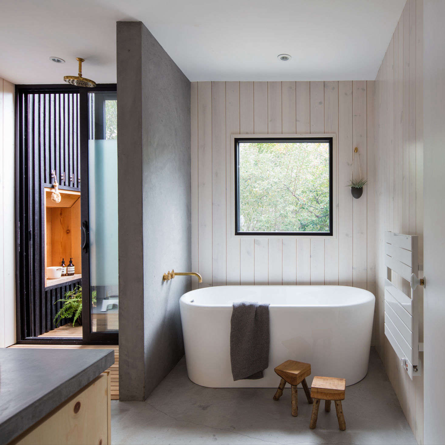A wall of rendered concrete plaster splits the shower from the bathtub. The concrete floors have radiant underfloor heating, and a towel warmer hangs on the wall by the bath.