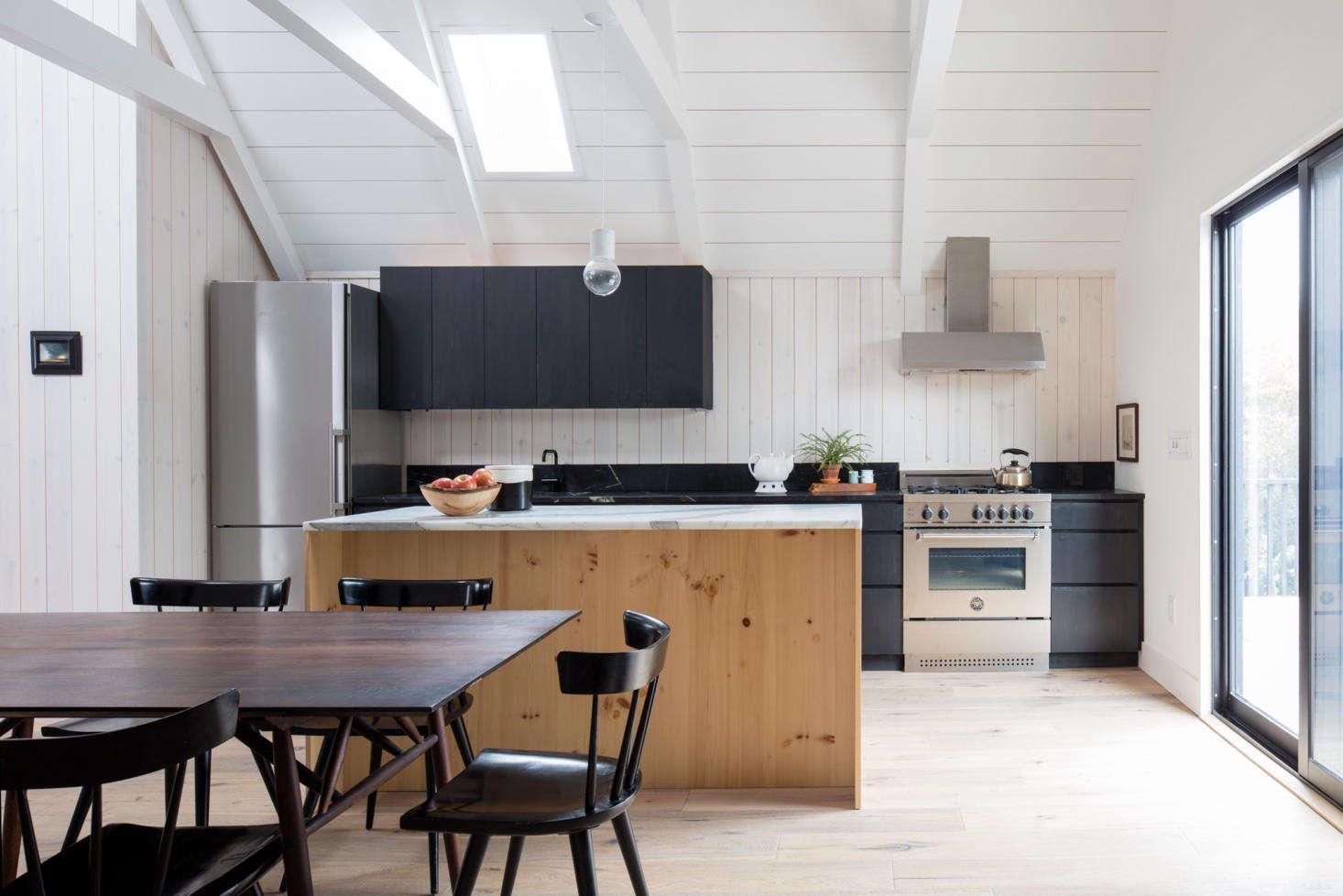 Though the kitchen is compact, it has a full suite of appliances, including a four-burnerBertazzoni range and a Bosch refrigerator (see  Easy Pieces: Best Skinny Refrigerators). The cabinets are pine wood, stained the same black color as the exterior cladding. &#8
