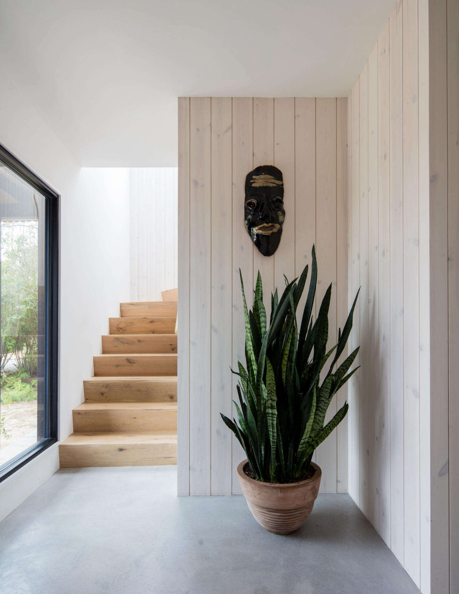 In the entryway a sansevieria plant sits beneath a mask collected on the couple&#8