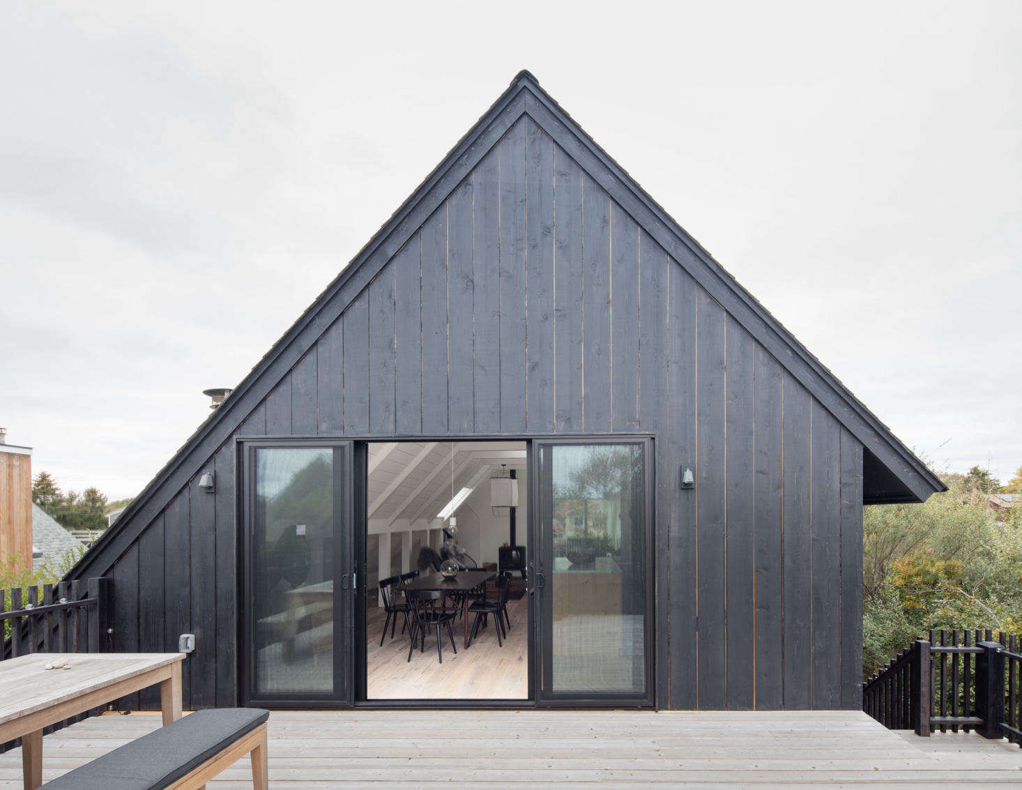 From the outset, the owners wanted the upper floor of the house to be an open-plan kitchen, living, and dining room with a link to the outdoors. It opens directly onto a back deck, which almost doubles that floor&#8