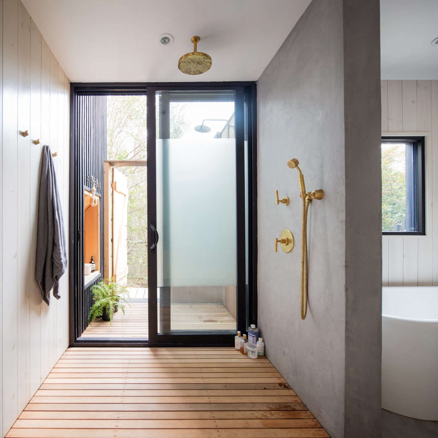 The ground-floor bath serves three bedrooms. It has both an indoor and outdoor shower, divided by anobscured-glass sliding door. The outdoor shower can be accessed from the side yard, so residents can have a post-beach rinse without coming indoors.