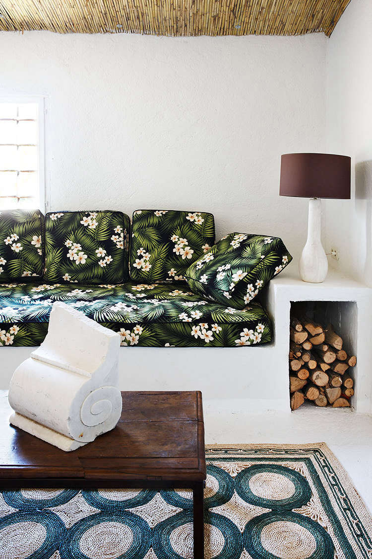 On one end of the room, an example of Castella's eclectic style: a built-in bench serves as both lounge space (with cushions upholstered in vintage floral fabric, found in Hawaii) and log storage for the nearby fireplace. An architectural remnant becomes sculpture on the low table.