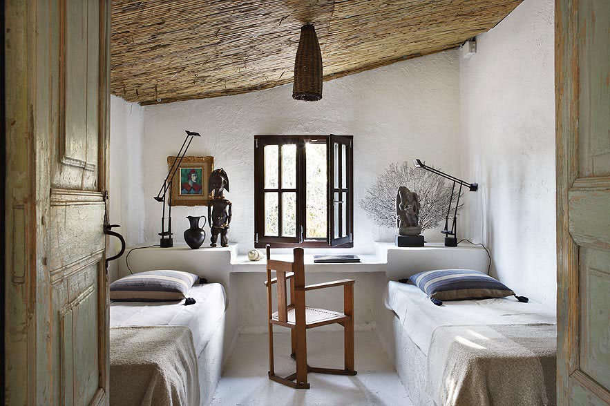 Beneath a sloped ceiling, twin beds are laid on built-in stone platforms and a shelf behind serves as both desk and headboard.
