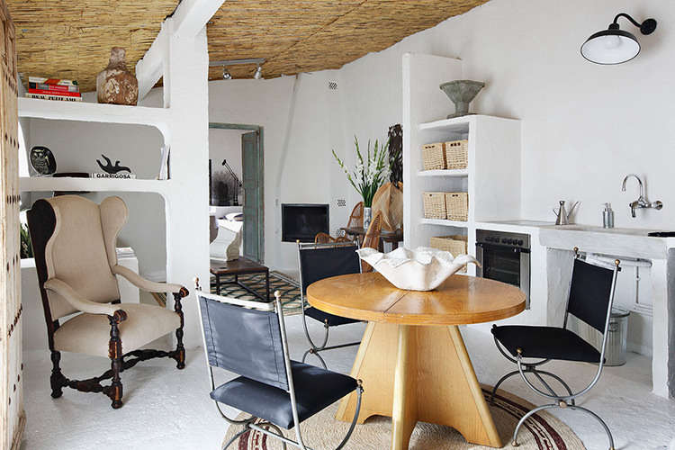 """The sculptural main room of the guest house, loosely divided by built-in shelves that extend from the walls. Castella wanted to transform the """"shell"""" of a stable into """"a memorable, Mediterranean environment,"""" someplace that would """"make you feel that you were on vacation on the sea."""" Castella also took cues from his own childhood summers spent on the Costa Brava with his grandparents."""