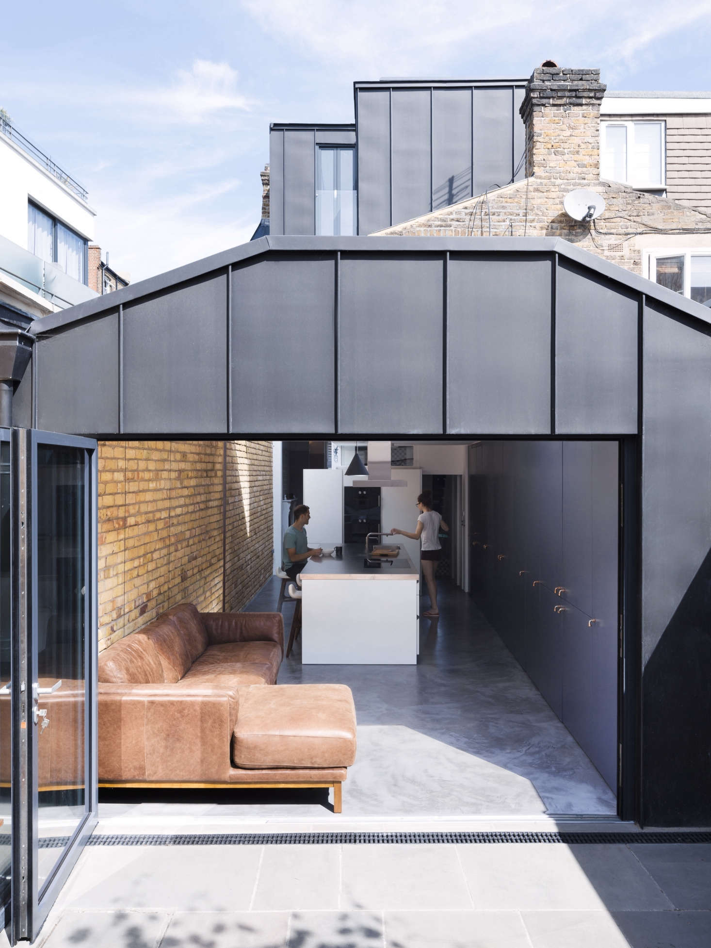 In the back of the house, in place of a small porch (scroll to the bottom for a Before shot), Astridge built a 350-square-foot kitchen/sitting area extension with an accordion steel-frame door that opens onto the terrace and garden.