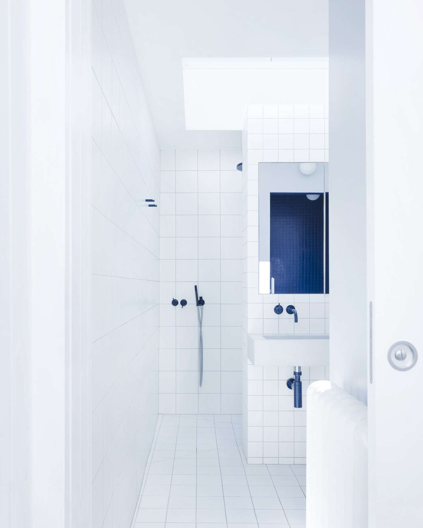 The en-suite blue-and-white master bath makes use of standard white tile in three sizes: the smallest on the sink wall, medium on the floor, and the largest on the central wall, all with gray grout.