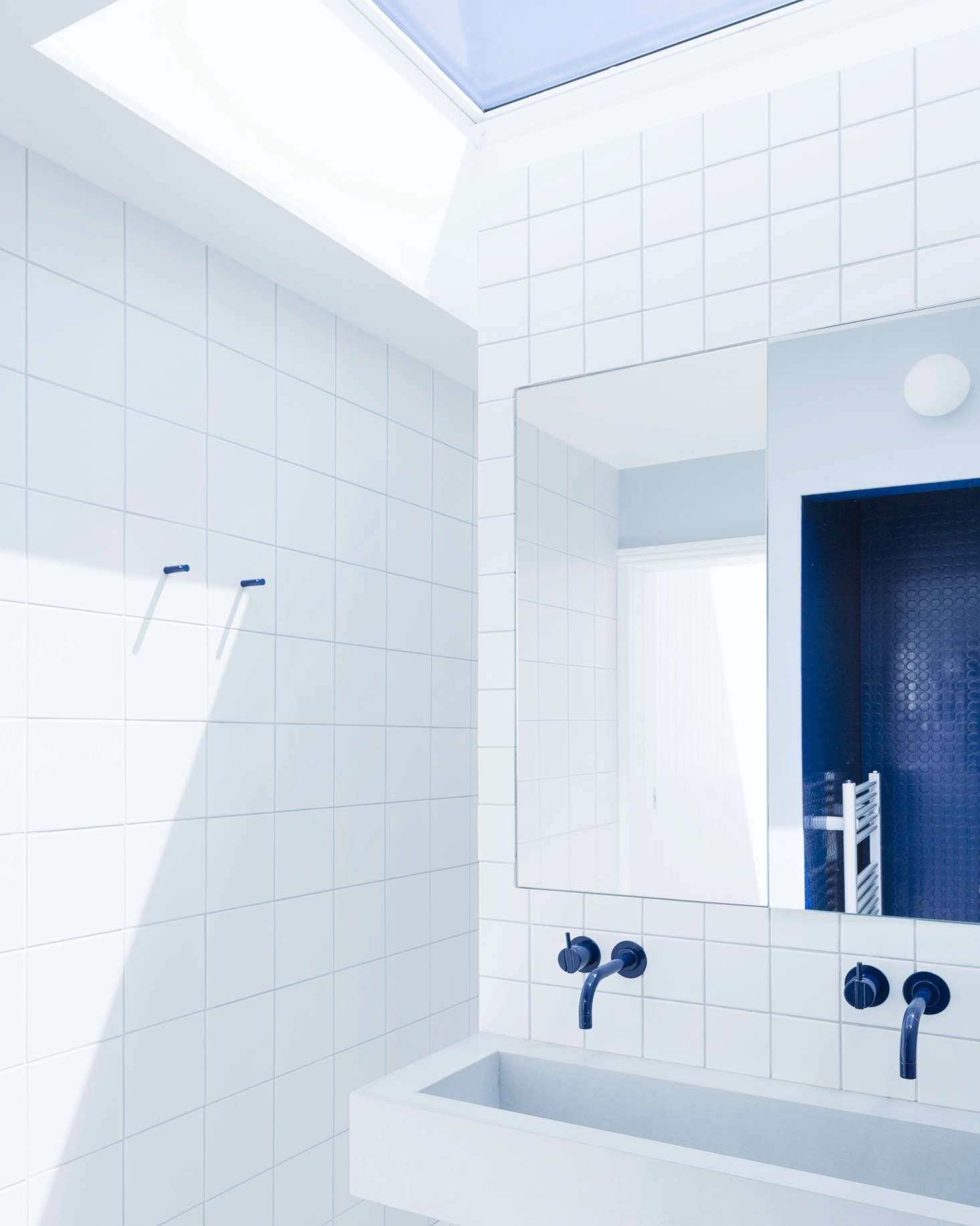 The room is divided into two halves by a tiled walk-around wall with a cast concrete sink made by the contractor, who also fabricated the medicine cabinets (reflected in the right is the WC clad in royal blue rubber flooring).