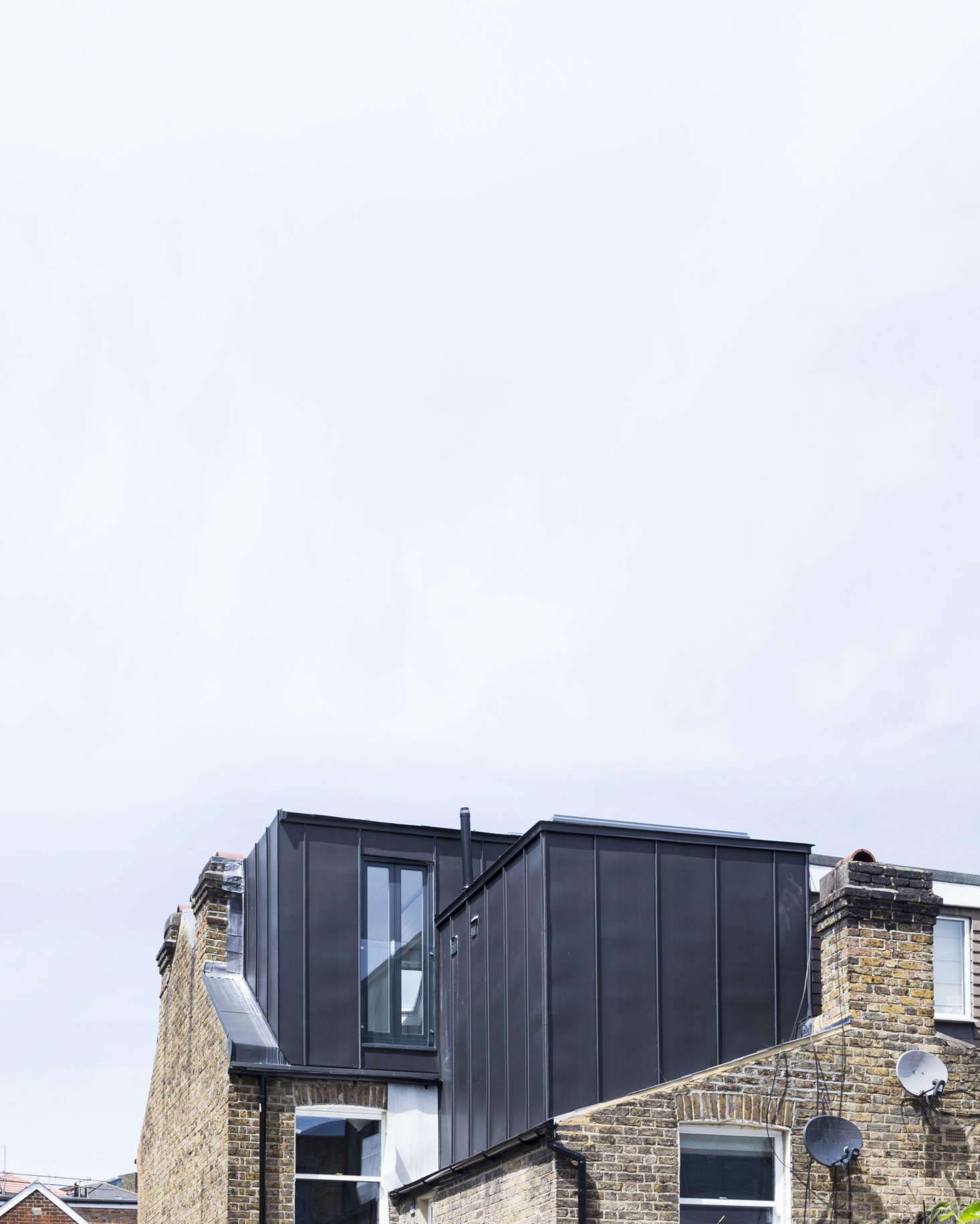 On the roof, two standing-seam metal additions extend the master bedroom and bath. The color was selected to work with the dark gray of the neighboring rooflines.