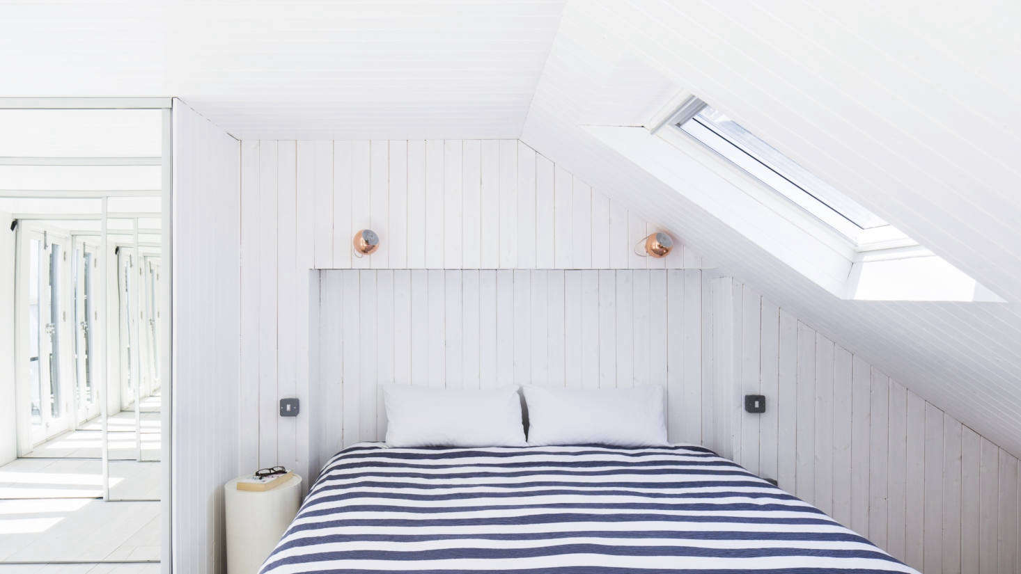 The whitewashed paneling continues in the under-the-eaves master bedroom, which integrates one of the roof extensions. A recess in the paneling takes the place of a headboard.
