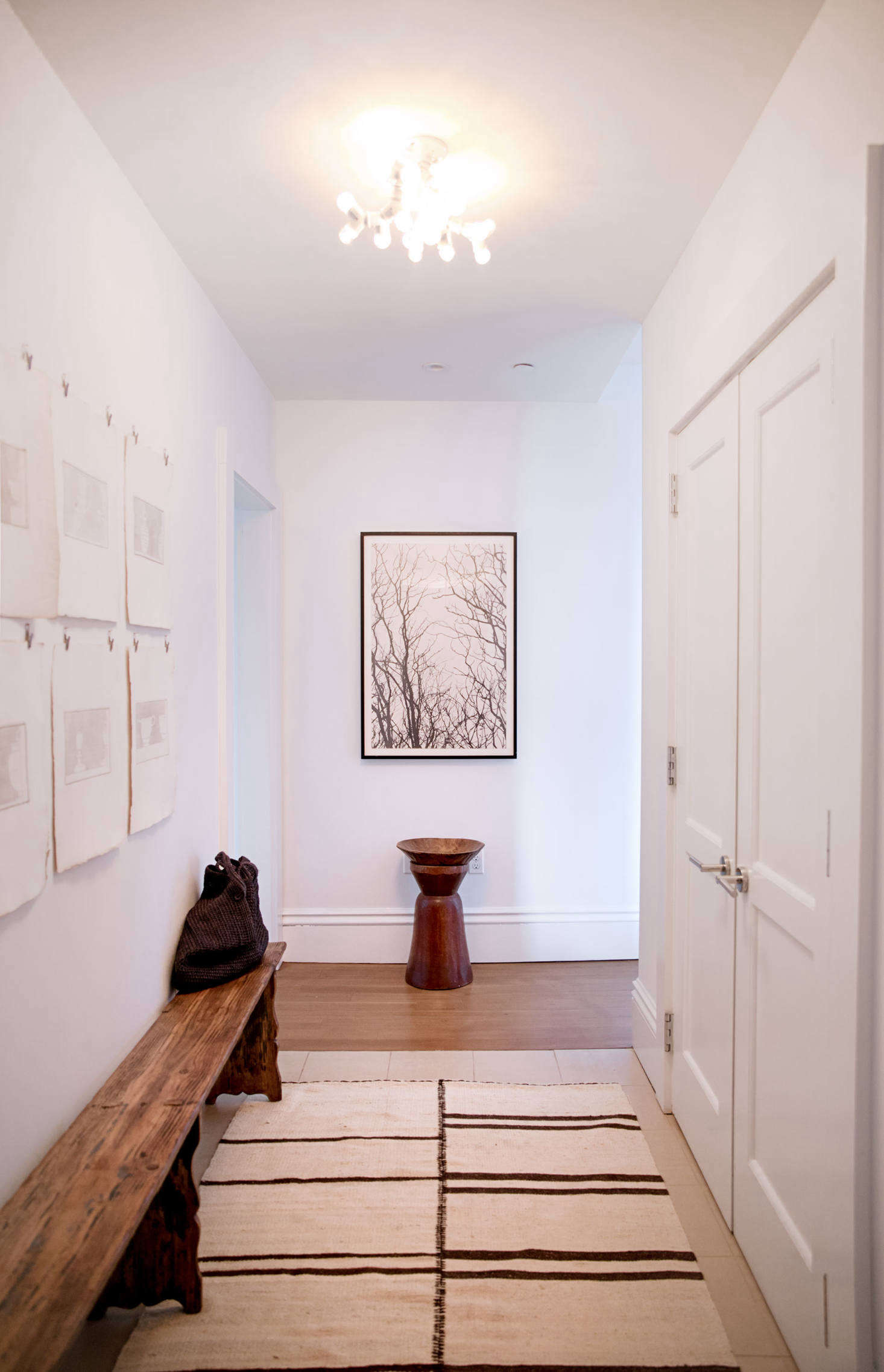 The entry hall is illuminated by a playful light that Jeffrey made from Home Depot parts.