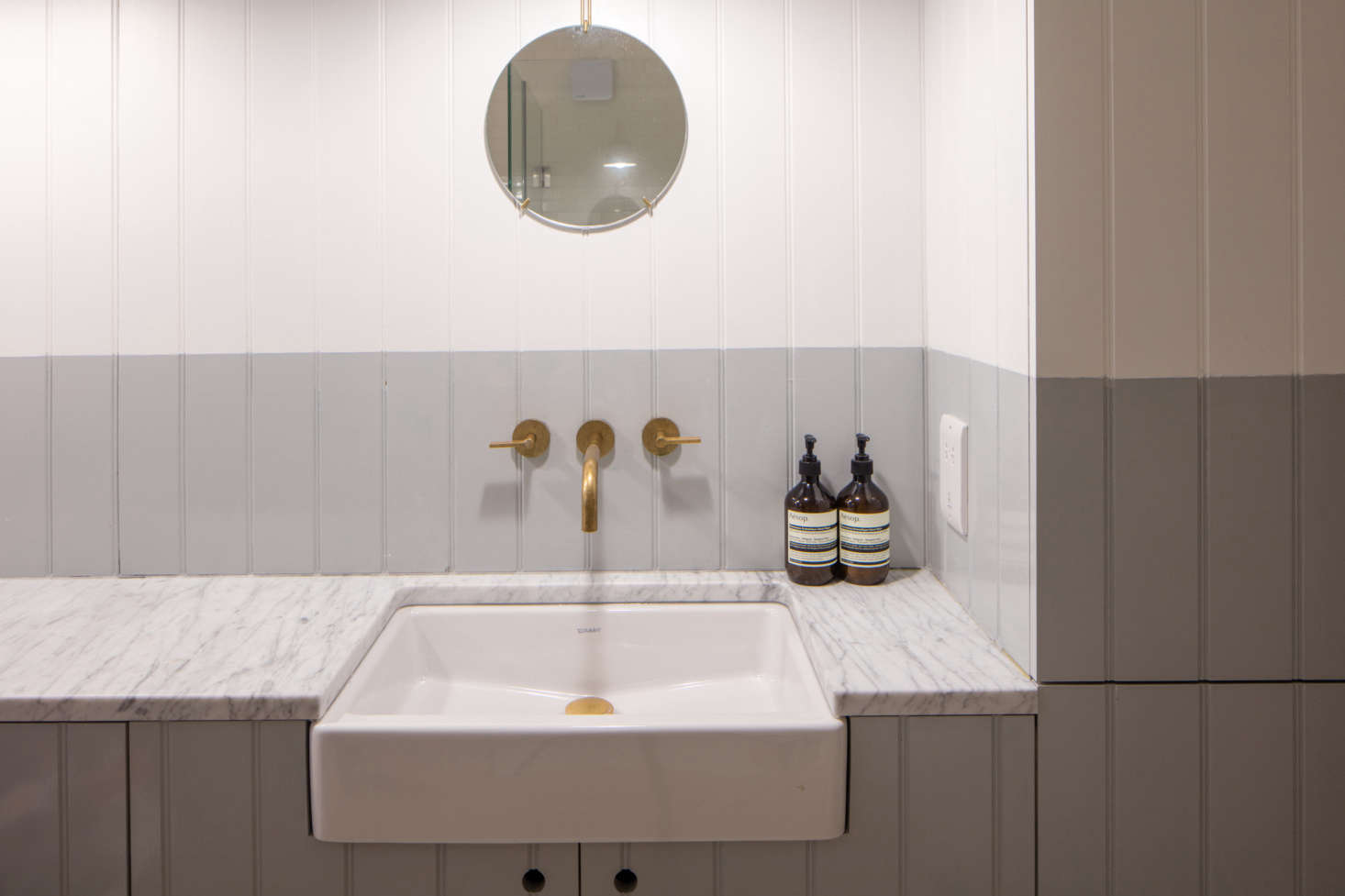 A bathroom is small but luxe with a marble counter. It's half-painted in Pure Grey 2 from Papers & Paints.