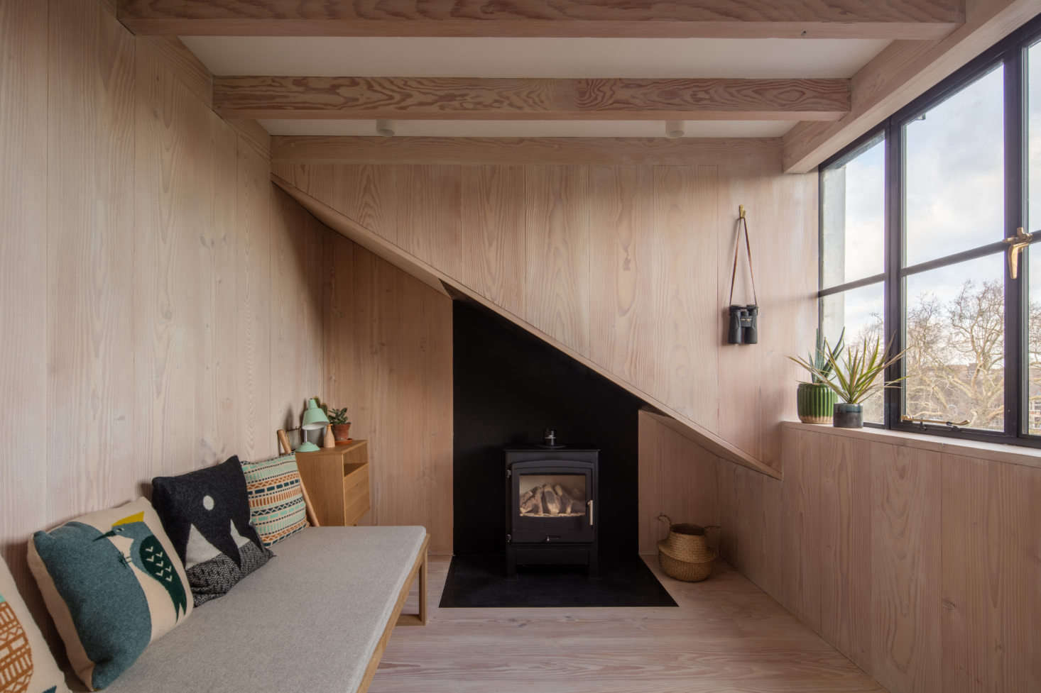 An upstairs bedroom/sitting room with another woodstove (note the black metal cladding that continues under the eaves).