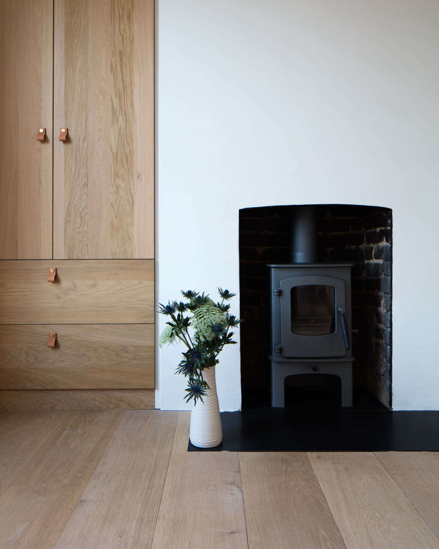 More evidence of the couple's predilection for wood-burning stoves. The cabinets are also Dinesen, designed by Tuck and built by Lionhead Construction. The leather cabinet pulls are Superfront'sLoop design.
