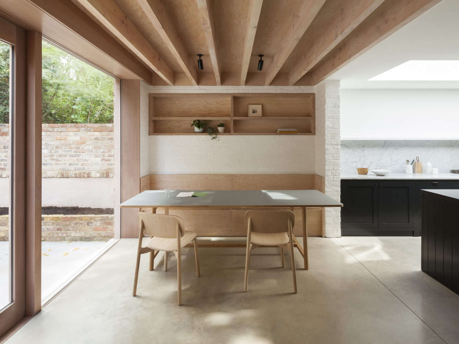 The dining area has a white slurried brick wall, a built-in banquette, and a recessed shelf in Douglas fir, with exposed joists above.