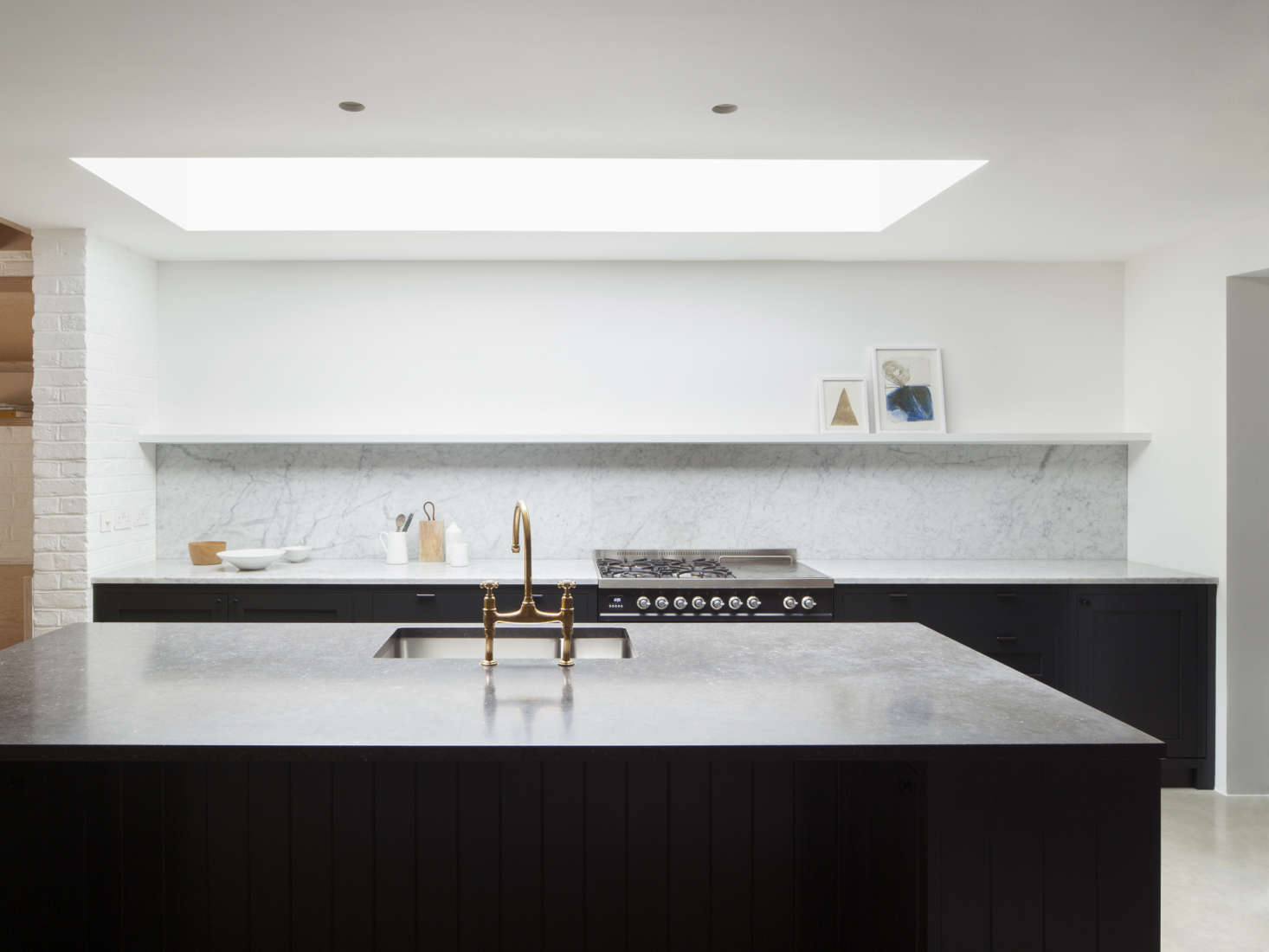 A new skylight over the kitchen helps to naturally illuminate the space, which is painted in Farrow & Ball Wimborne White—just one shade away from pure white. The custom cabinets by Handmade Kitchens are finished in blue-black Railings paint, also by Farrow & Ball. The Carrara marble counter and backsplash are from Rossi Stoneworks and the island top is Belgian bluestone. The range is the Ilve Roma Twin Range Cooker; it's the only visible appliance in the kitchen; others are panel-ready Bosch appliances. The island faucet is Perrin & Rowe&#8