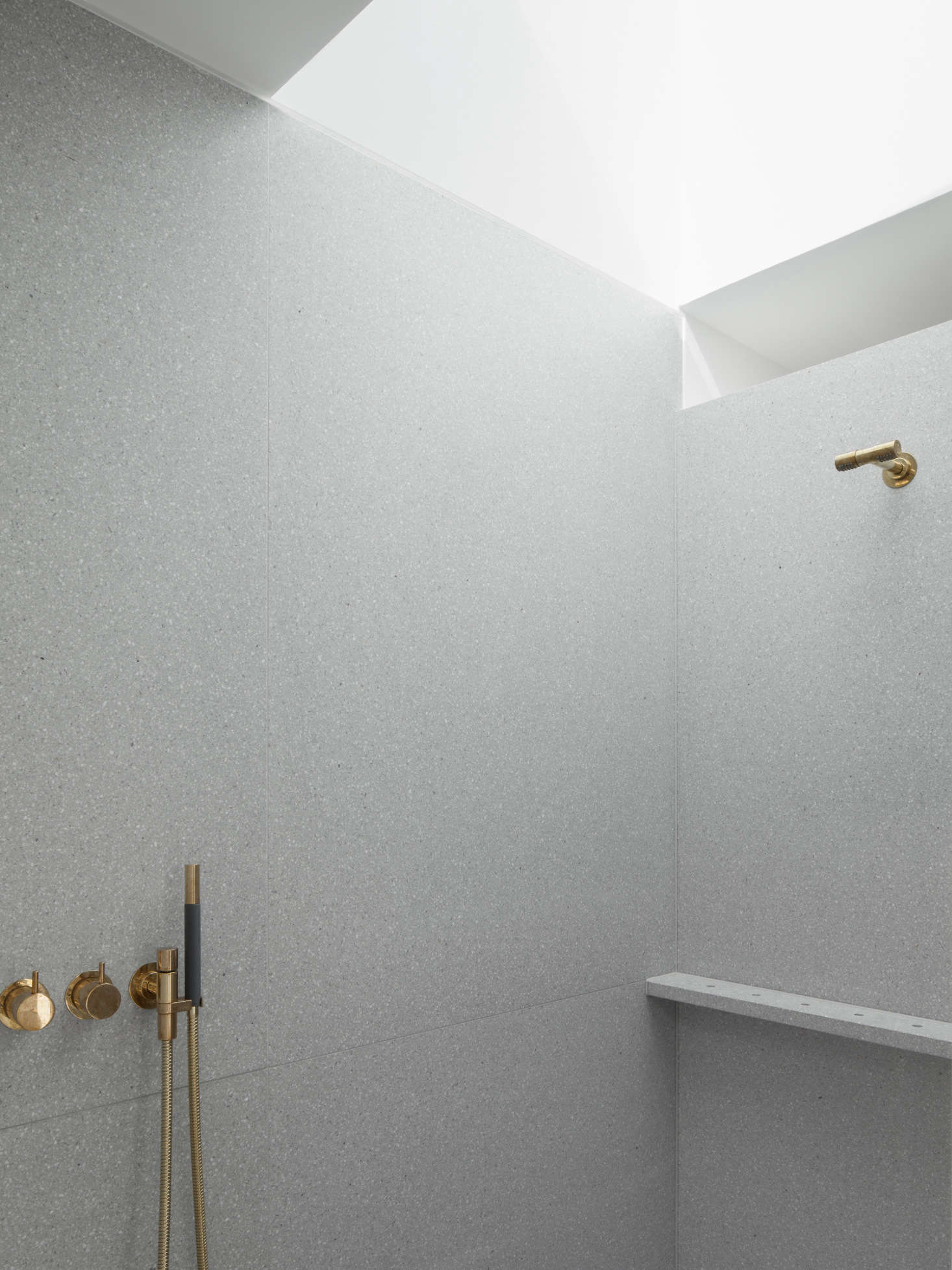 The shower is clad in Terrazzo Cement and outfitted with a Vola Thermostatic Mixer (547src=