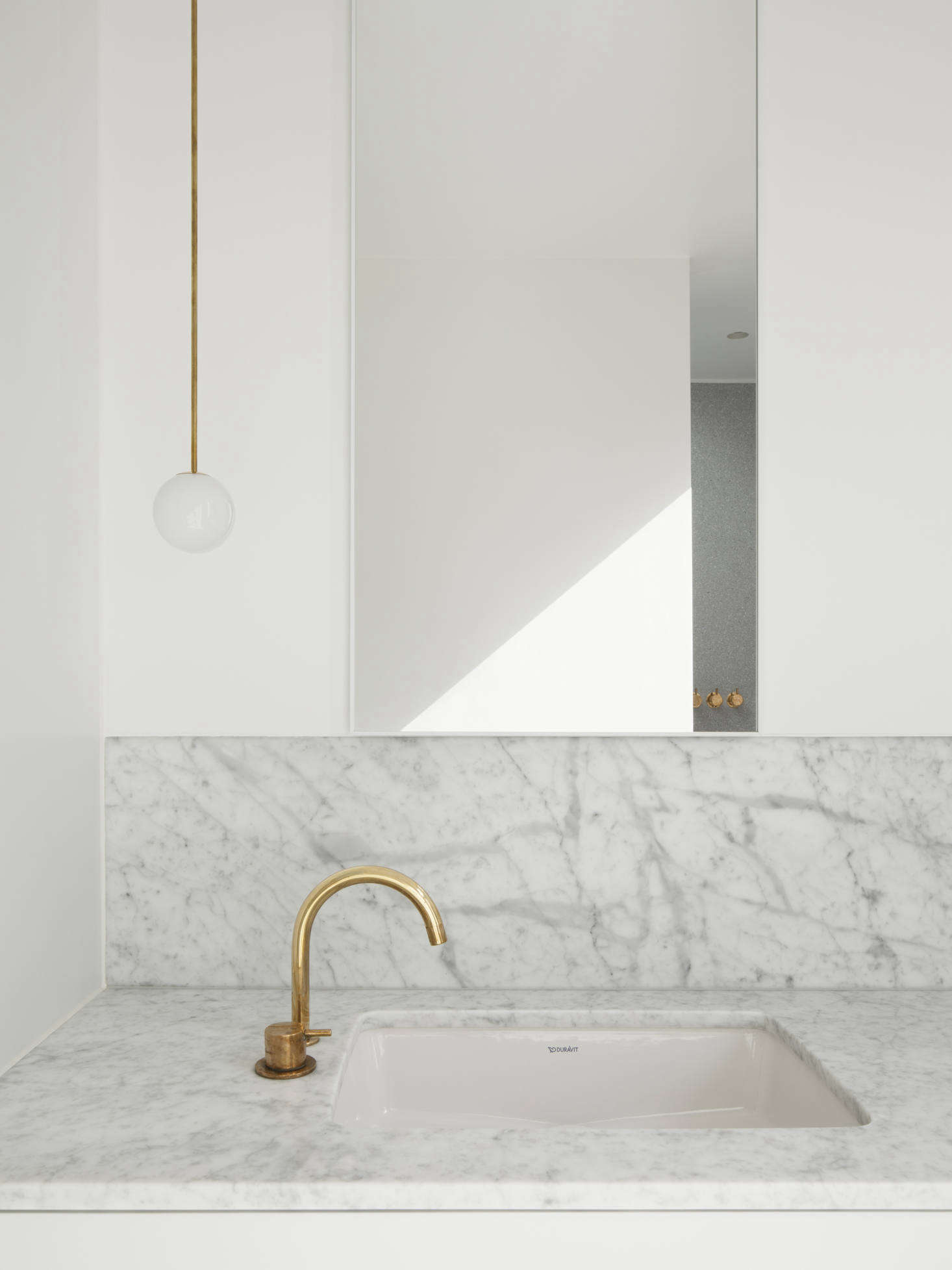 The faucet is a Vola One Handle Mixer 590V in natural brass and the sink is the Duravit D-Code Vanity Basin. The light is Michael Anastassiades's Brass Pendant 80 Rod.